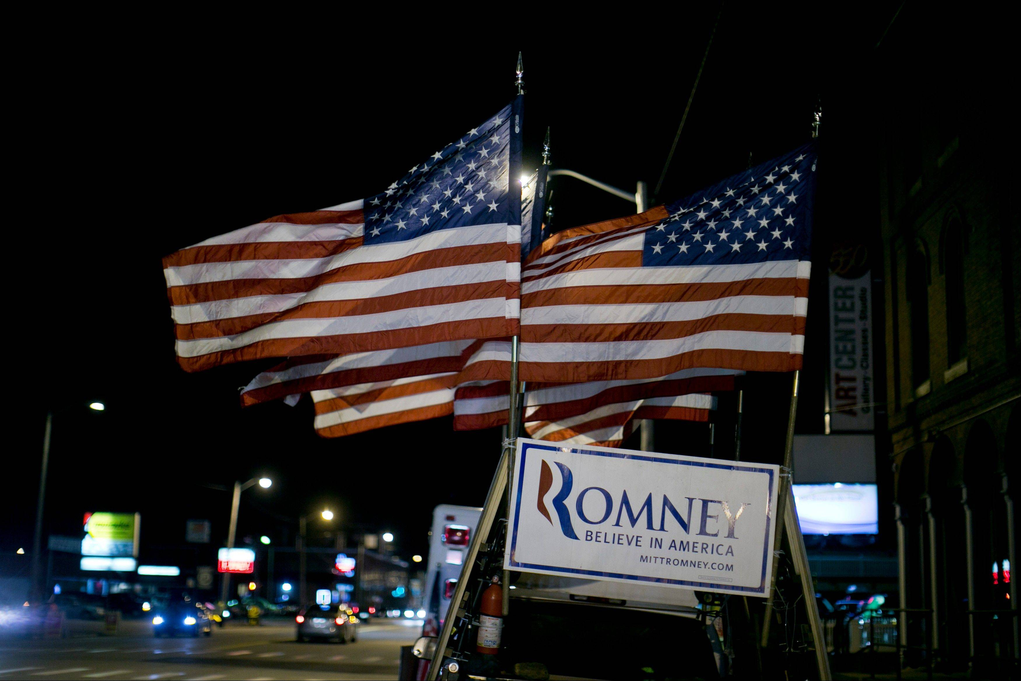 Flags fly above a sign for Republican presidential candidate Mitt Romney on a truck prior to a Romney campaign rally at the Verizon Wireless Center in Manchester, New Hampshire, U.S., on Monday.