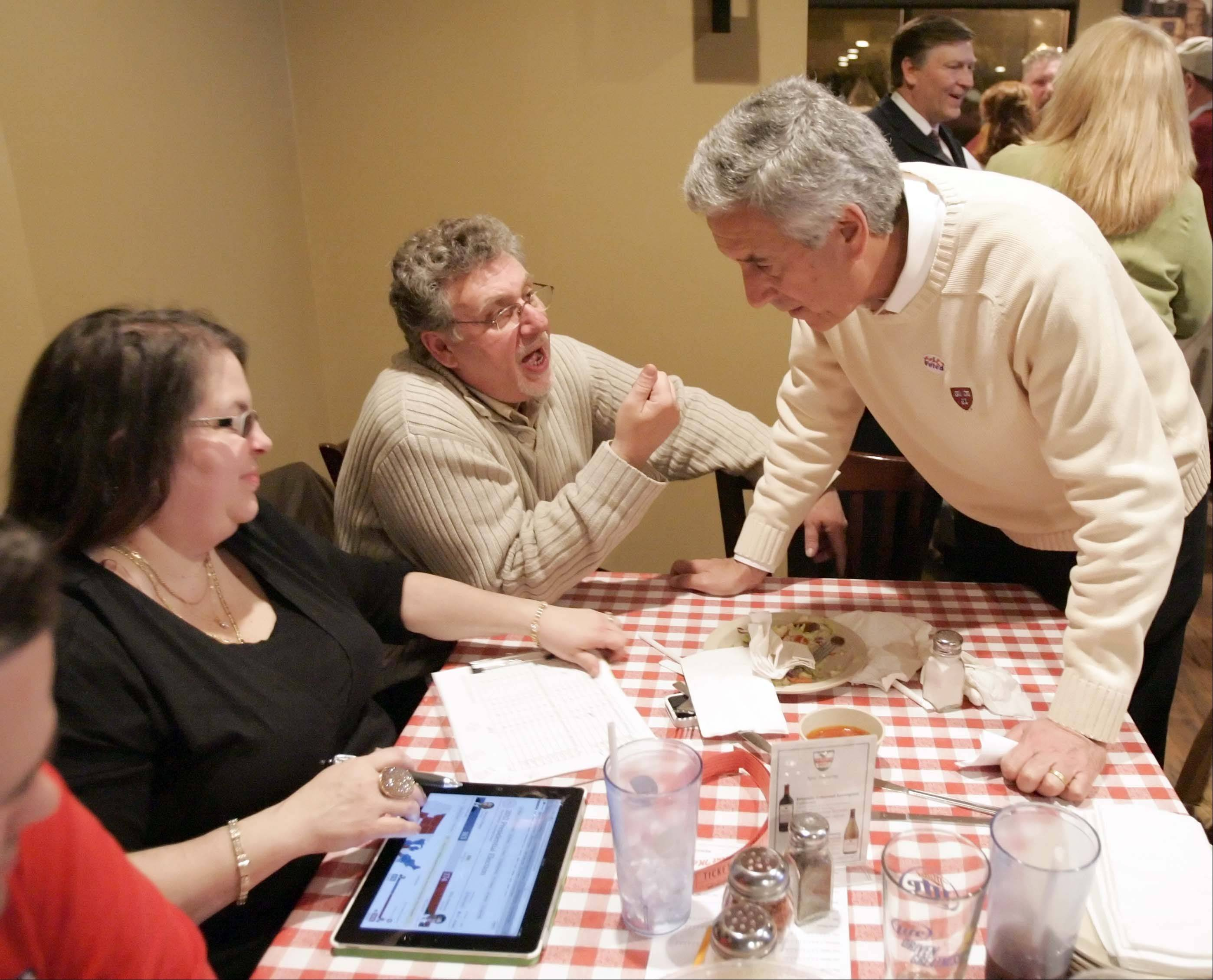 Chris Lauzen looks over results Tuesday with Sal and Christina Abbate of North Aurora at Aurelio's Pizza in Geneva. Lauzen defeated Sue Klinkhamer for the Kane County Board chairman's seat.