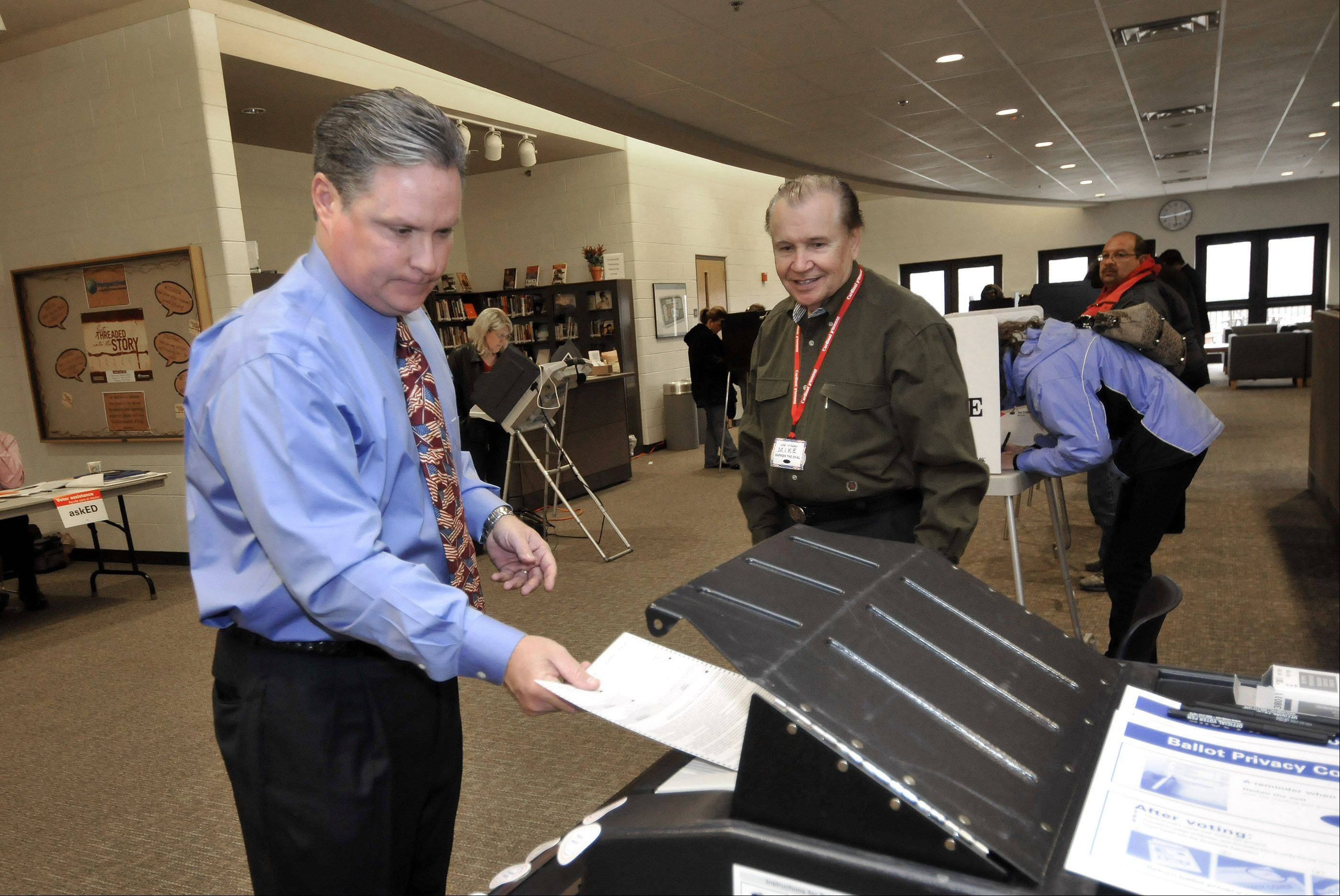 DuPage County Board member Jim Zay, left, casts his ballot on Tuesday morning at his polling place in West Chicago while election official Mike Bodnar watches. Zay won re-election to his District 6 seat.
