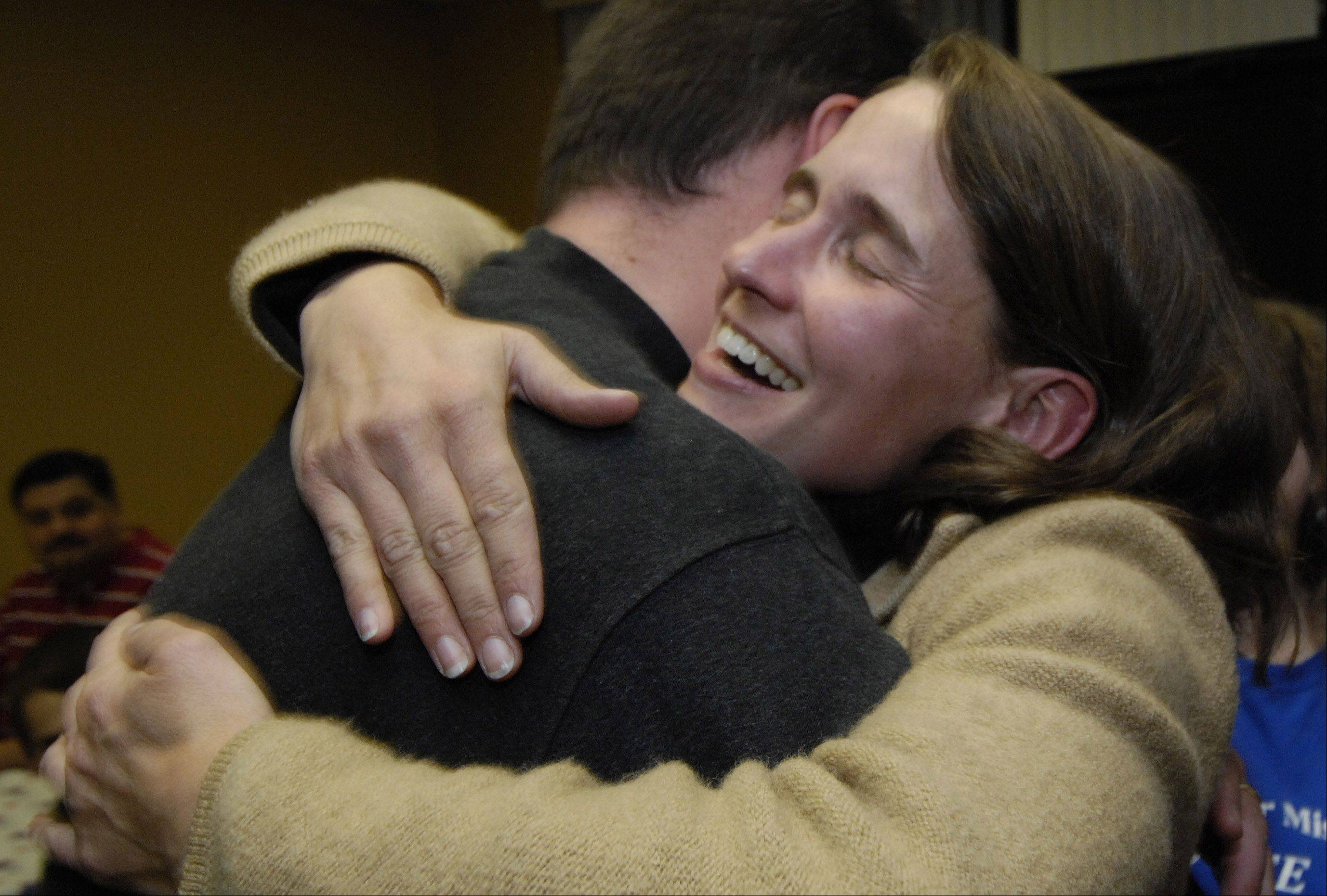 JOE LEWNARD/jlewnard@dailyherald.comMichelle Mussman hugs her husband, George, at her campaign headquarters in Schaumburg Tuesday after receiving word that she won re-election in the 56th District Illinois House race.