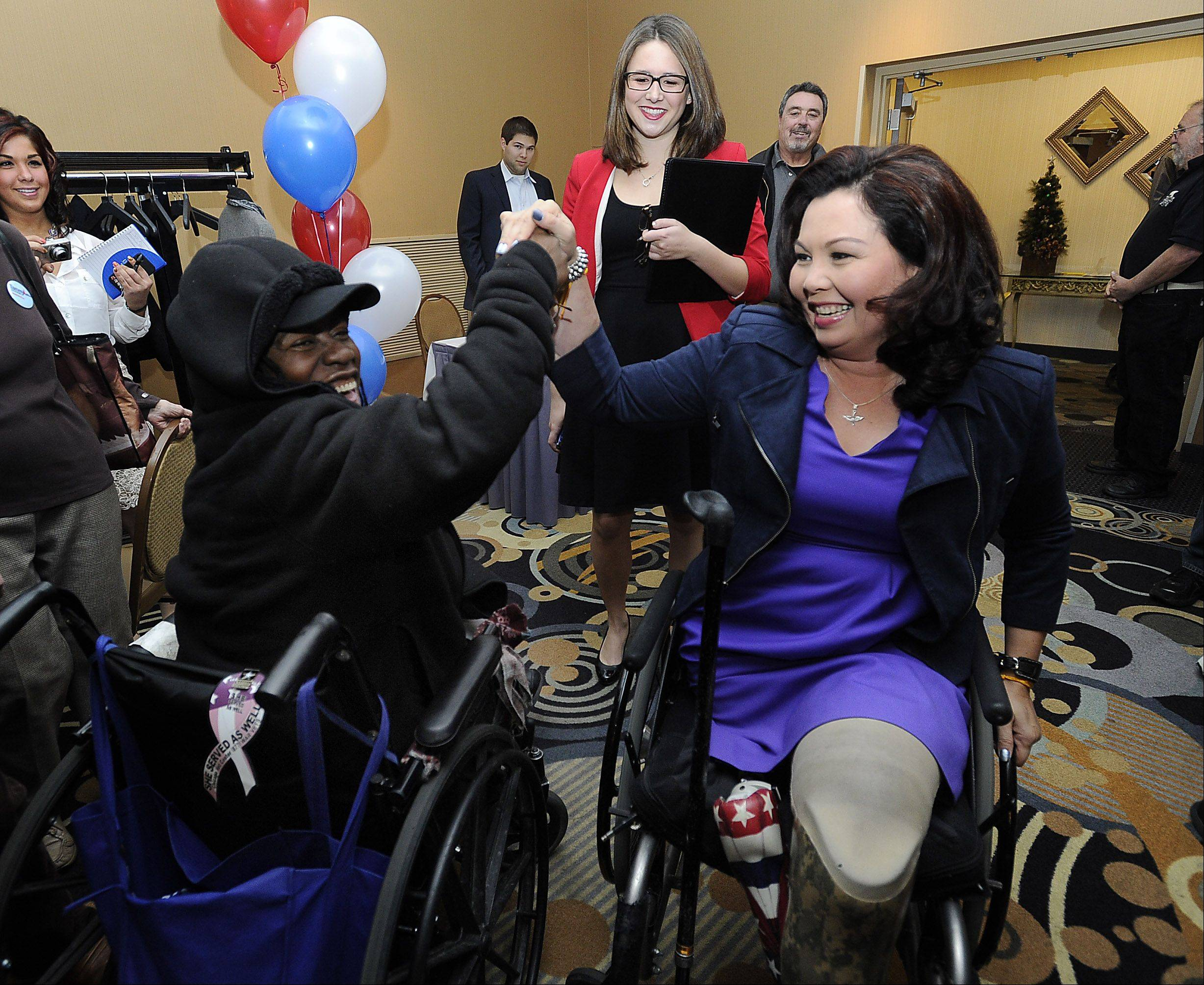 Mark Welsh/mwelsh@dailyherald.com Tammy Duckworth enters her campaign headquarters at the Holiday Inn in Elk Grove Village to the cheers and a best wishes from fellow veteran Octavia Mitchell of Chicago as she prepares to talk to the media.