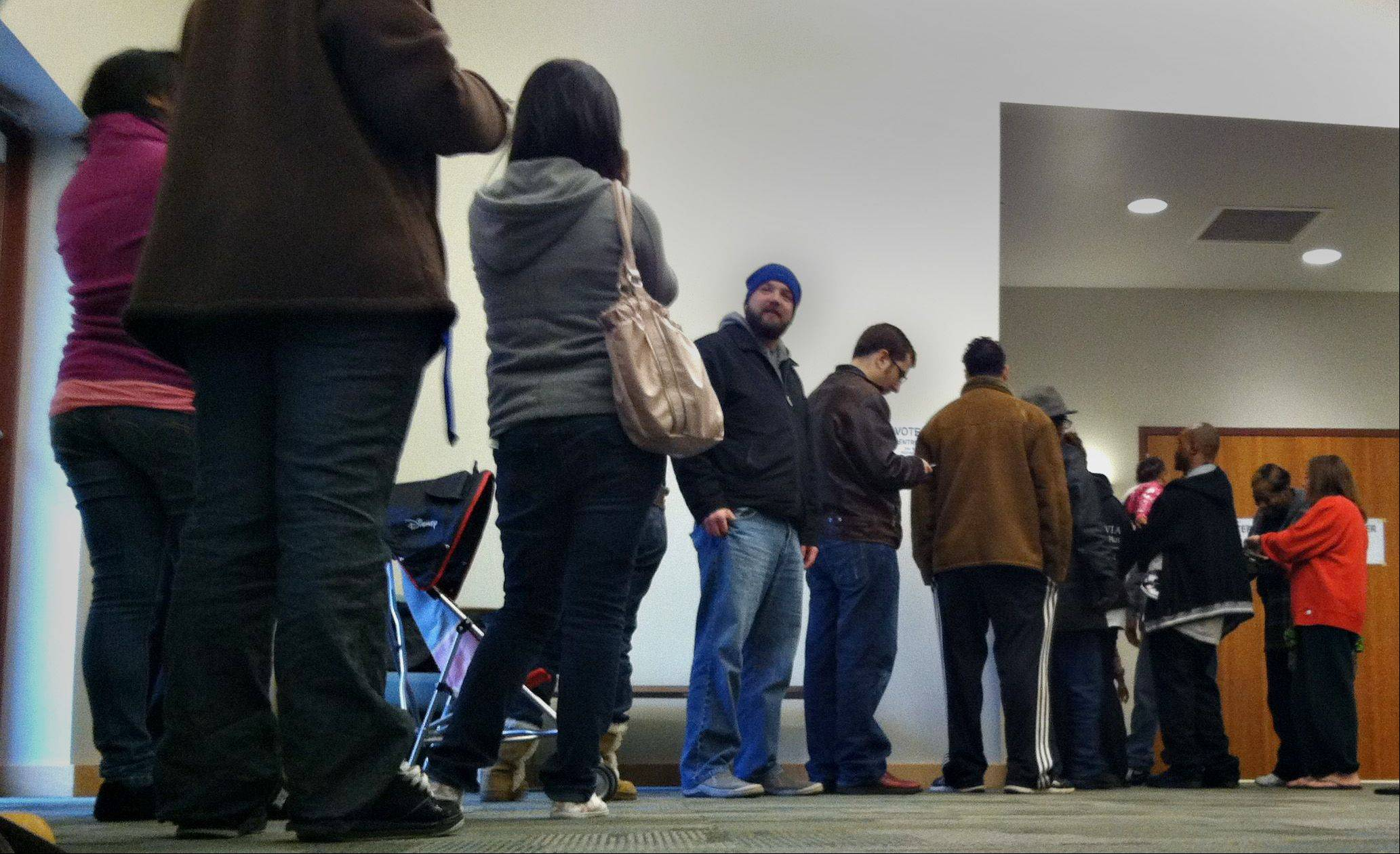 A line of voters wait inside the Gail Borden Public Library Tuesday morning on election day.