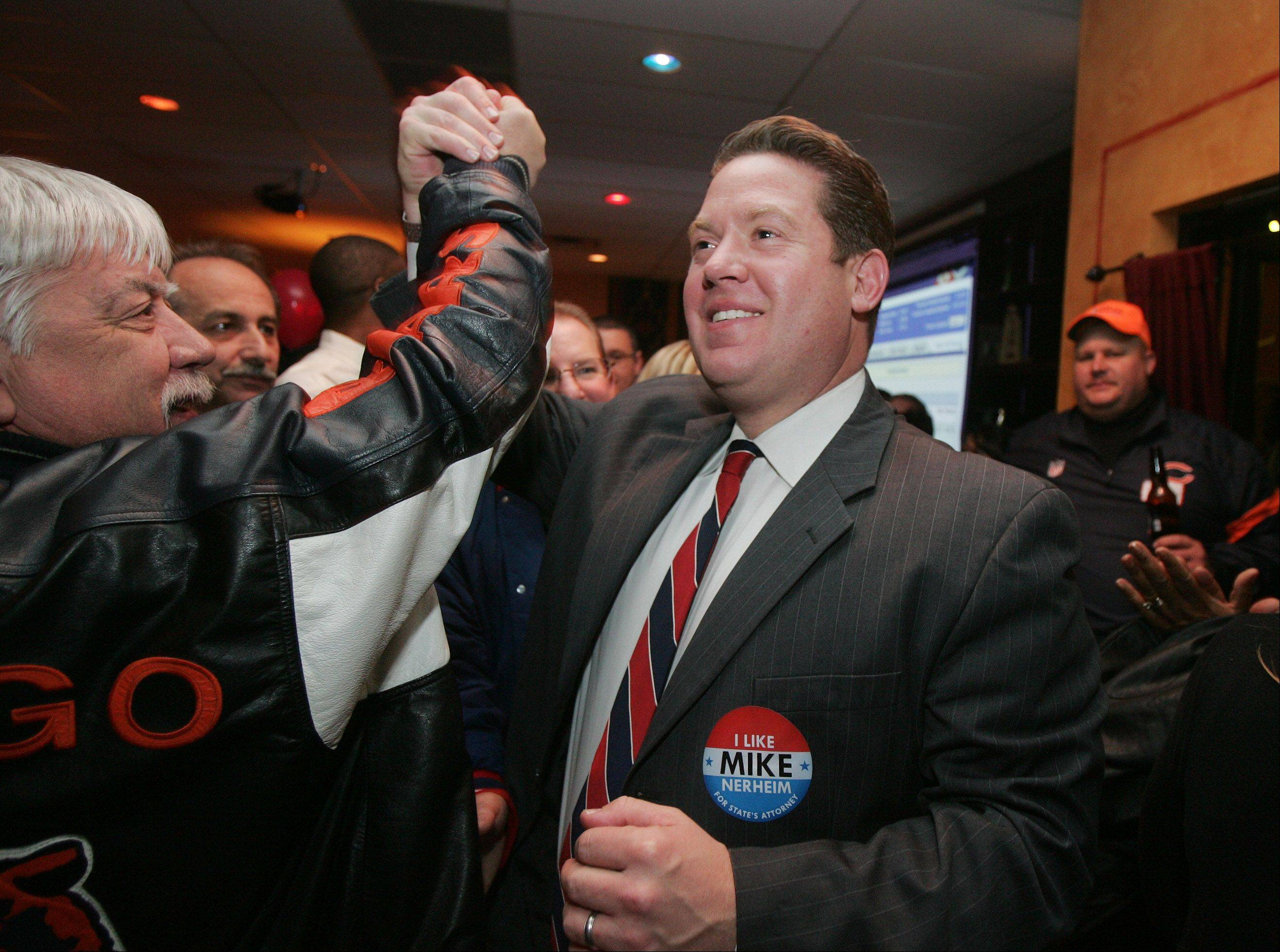 Republican candidate Mike Nerheim's hand is lifted in victory by supporter Tom Briscoe before he gives his victory speech at Tacos El Norte in Gurnee Tuesday after he won the Lake County State's Attorney's race.