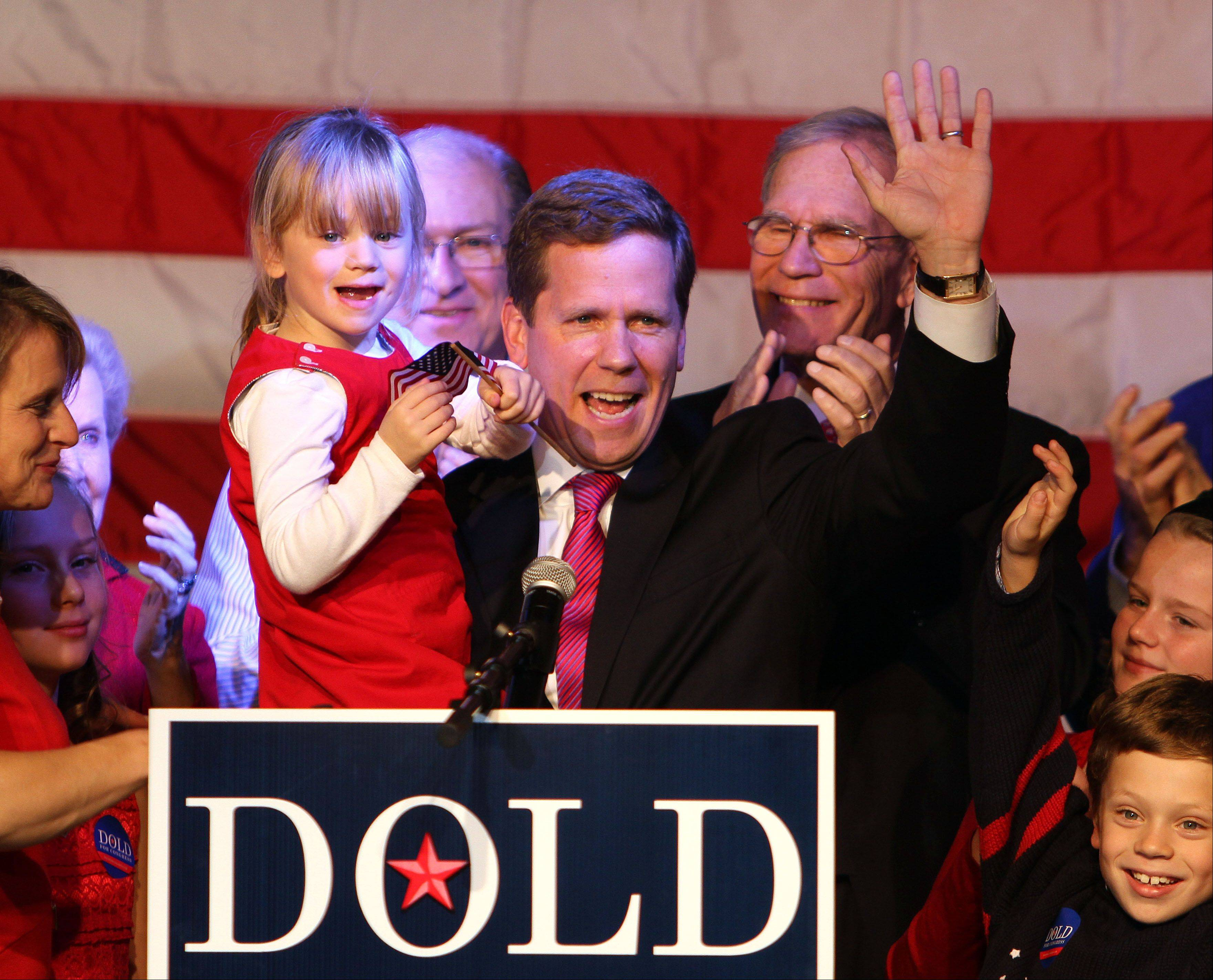 Republican 10th Congressional candidate Robert Dold holds his daughter Honor after losing to Brad Schneider at Viper Alley in Lincolnshire Tuesday night.