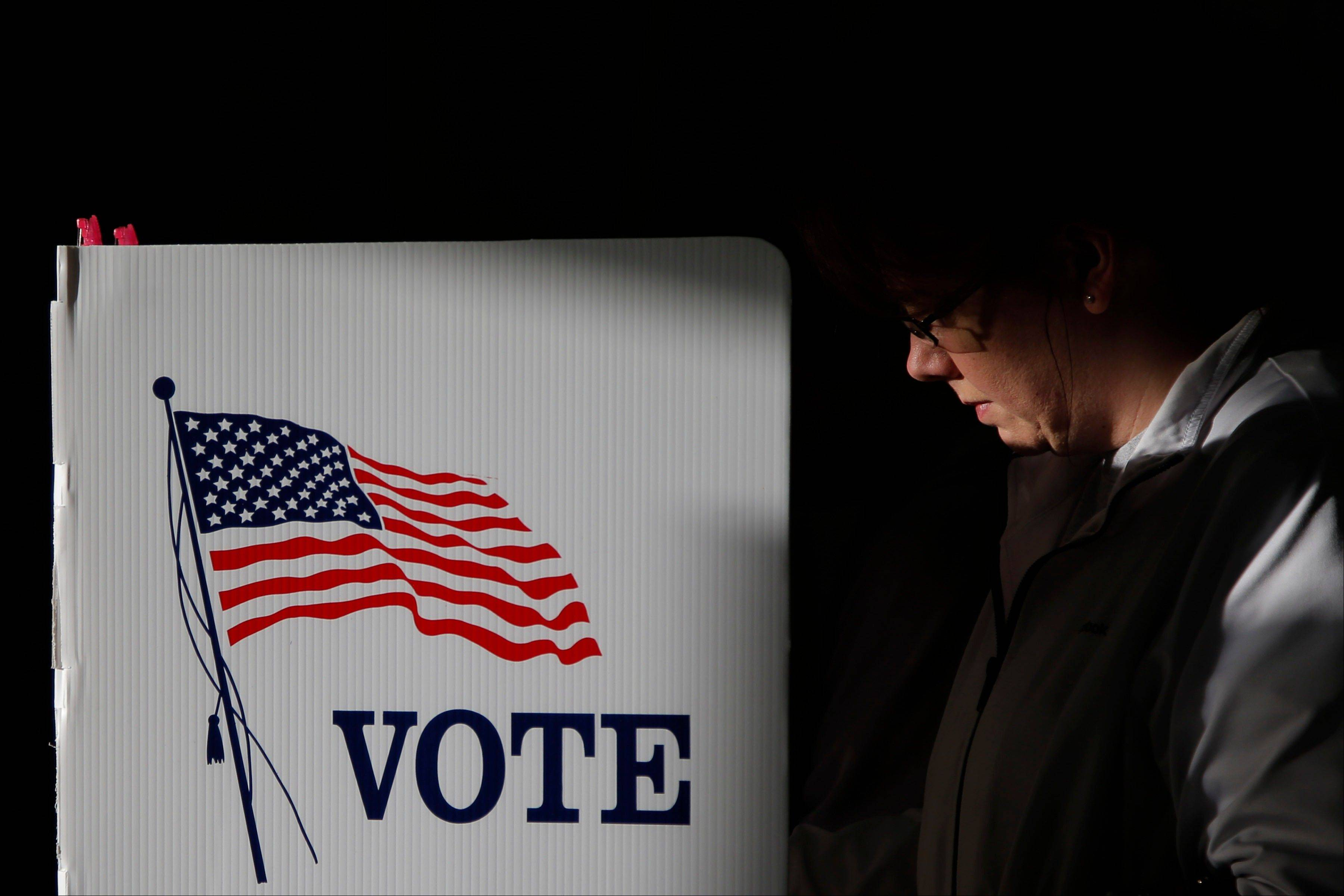 Kristi Voegele is illuminated by sunlight as she casts a ballot at a polling place in Billings, Mont., Tuesday, Nov. 6, 2012.