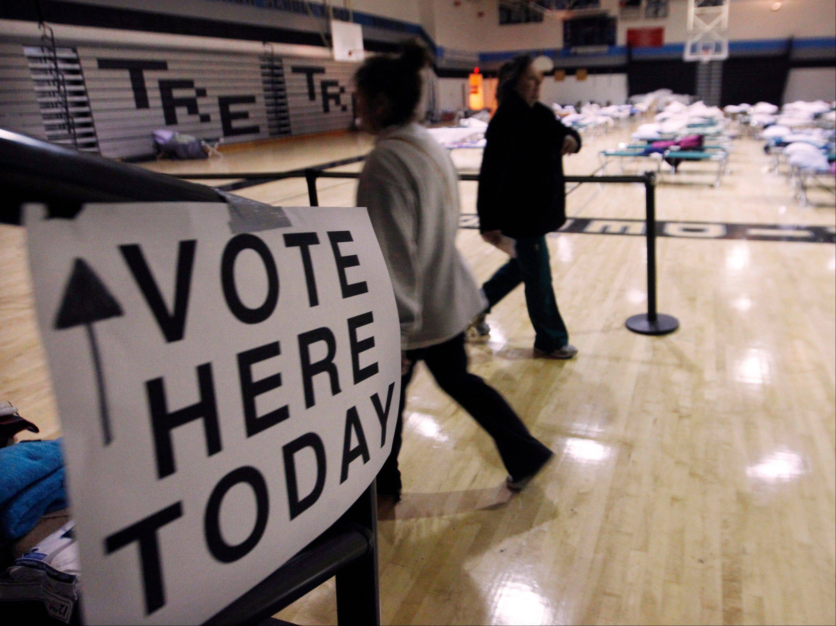 People walk through a makeshift shelter in a gymnasium at Toms River East High School as they arrive to vote Tuesday, Nov. 6, 2012, in Toms River, N.J. Voter turnout was heavy in several storm-ravaged Jersey Shore towns, with many voters expressing relief and even elation at being able to vote at all, considering the devastation.