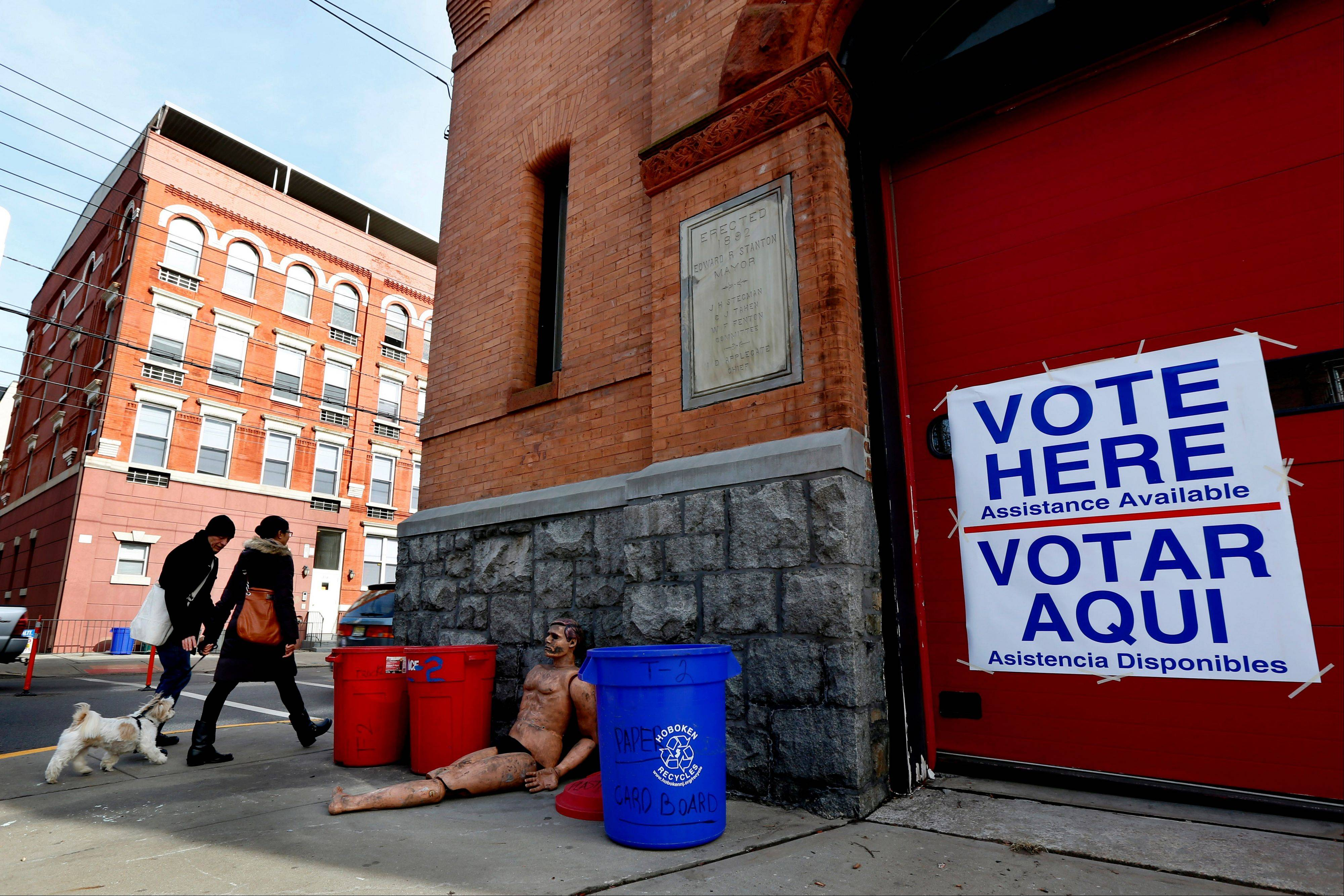 People walk with a dog toward the main entrance of a polling place at a Hoboken Fire Department firehouse on Election Day, Tuesday, Nov. 6, 2012, in Hoboken, N.J.