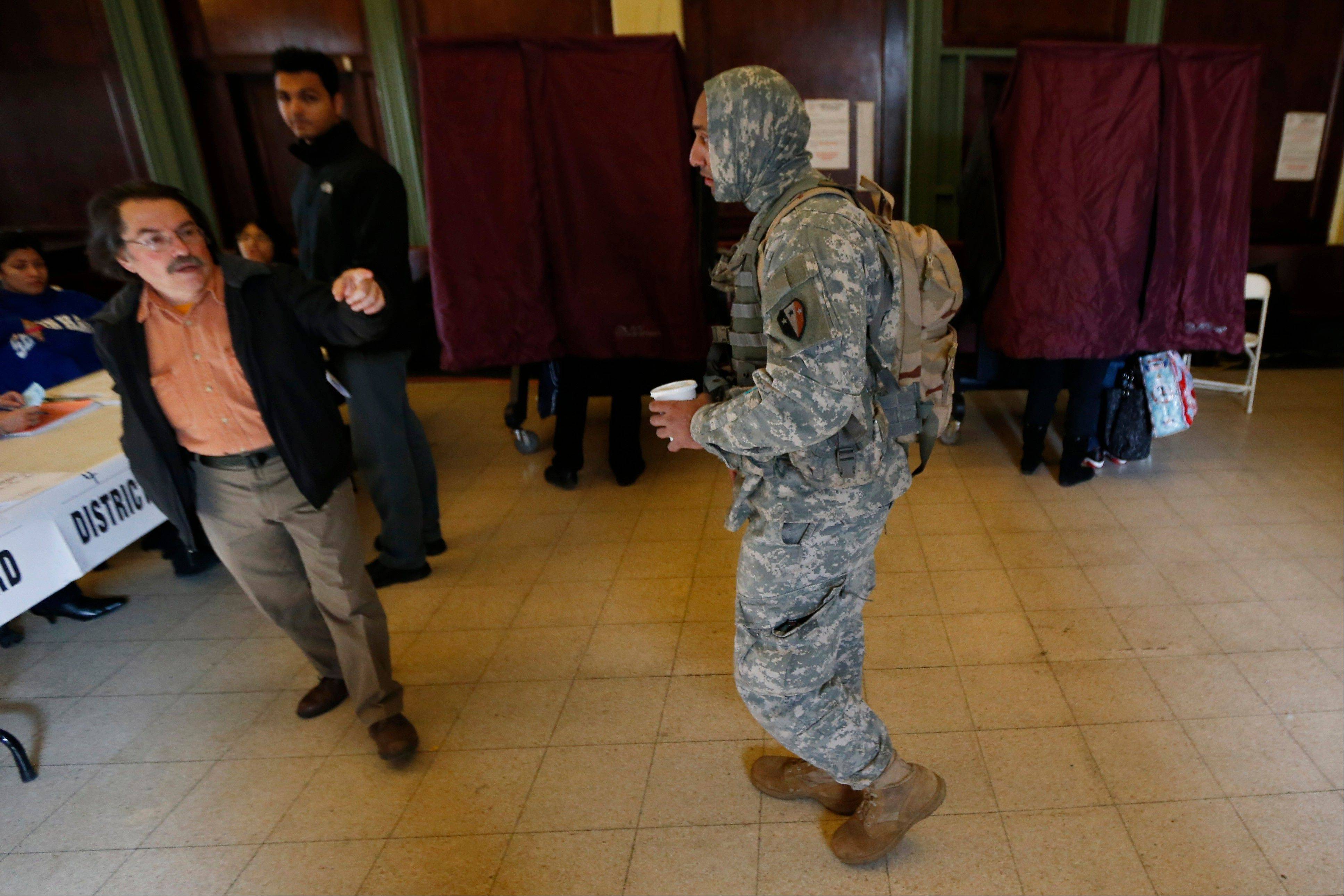 Polling place worker Ira Landgarten, left, directs New Jersey National Guard Spc. Cullin King, right, of Hillside, N.J., as he arrives at Hoboken City Hall to fill out an affidavit to cast his vote on Election Day, Tuesday, Nov. 6, 2012, in Hoboken, N.J. The National Guard members are performing duties in the city, which was hit by severe flooding caused by Superstorm Sandy.