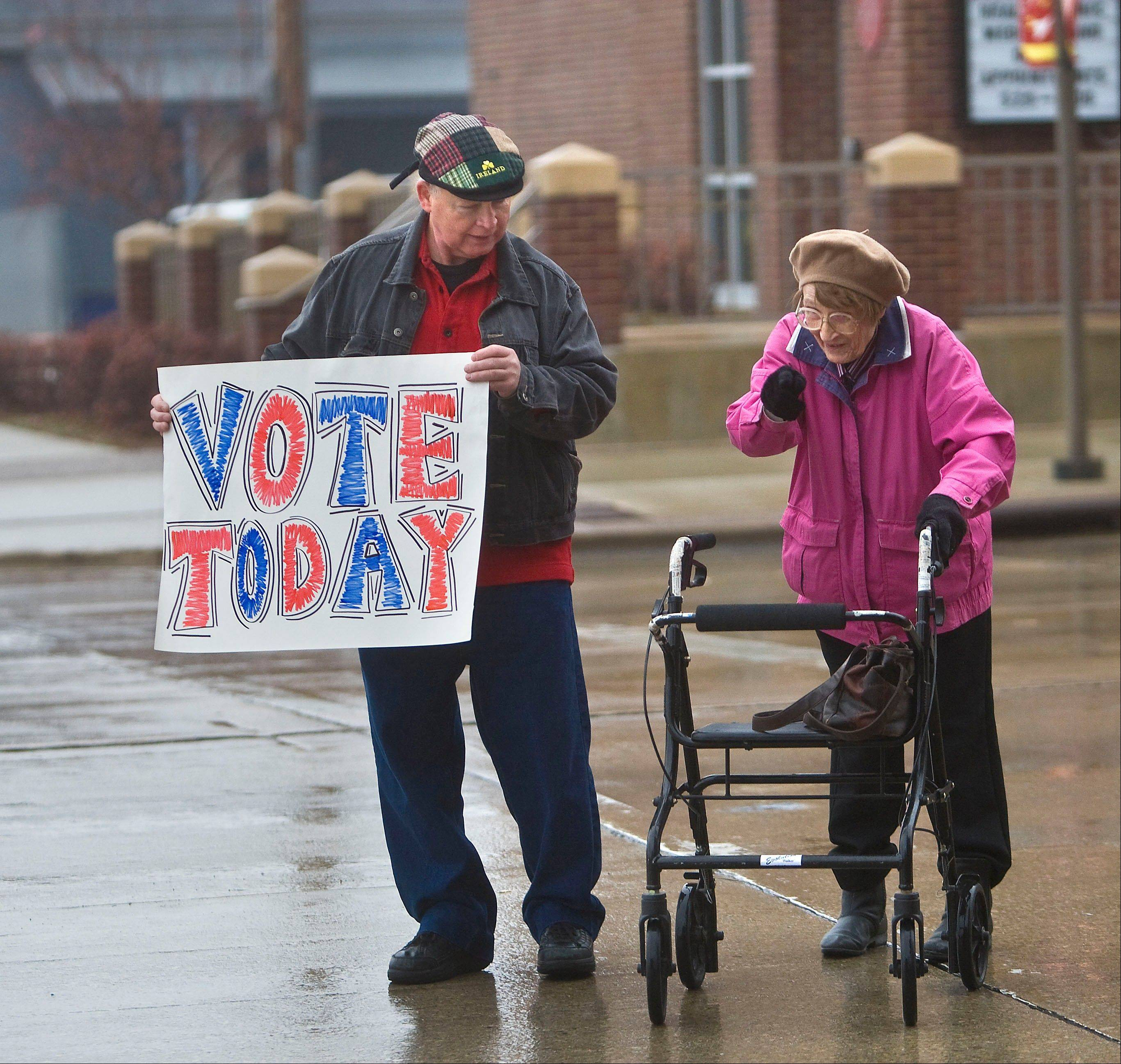 Mike Maloney briefly stops traffic so Elizabeth Rahn can cross the street to get to her polling place, outside the Rochester Senior Center, Tuesday, Nov. 6, 2012 in Rochester, Minn. Maloney was encouraging people to vote.