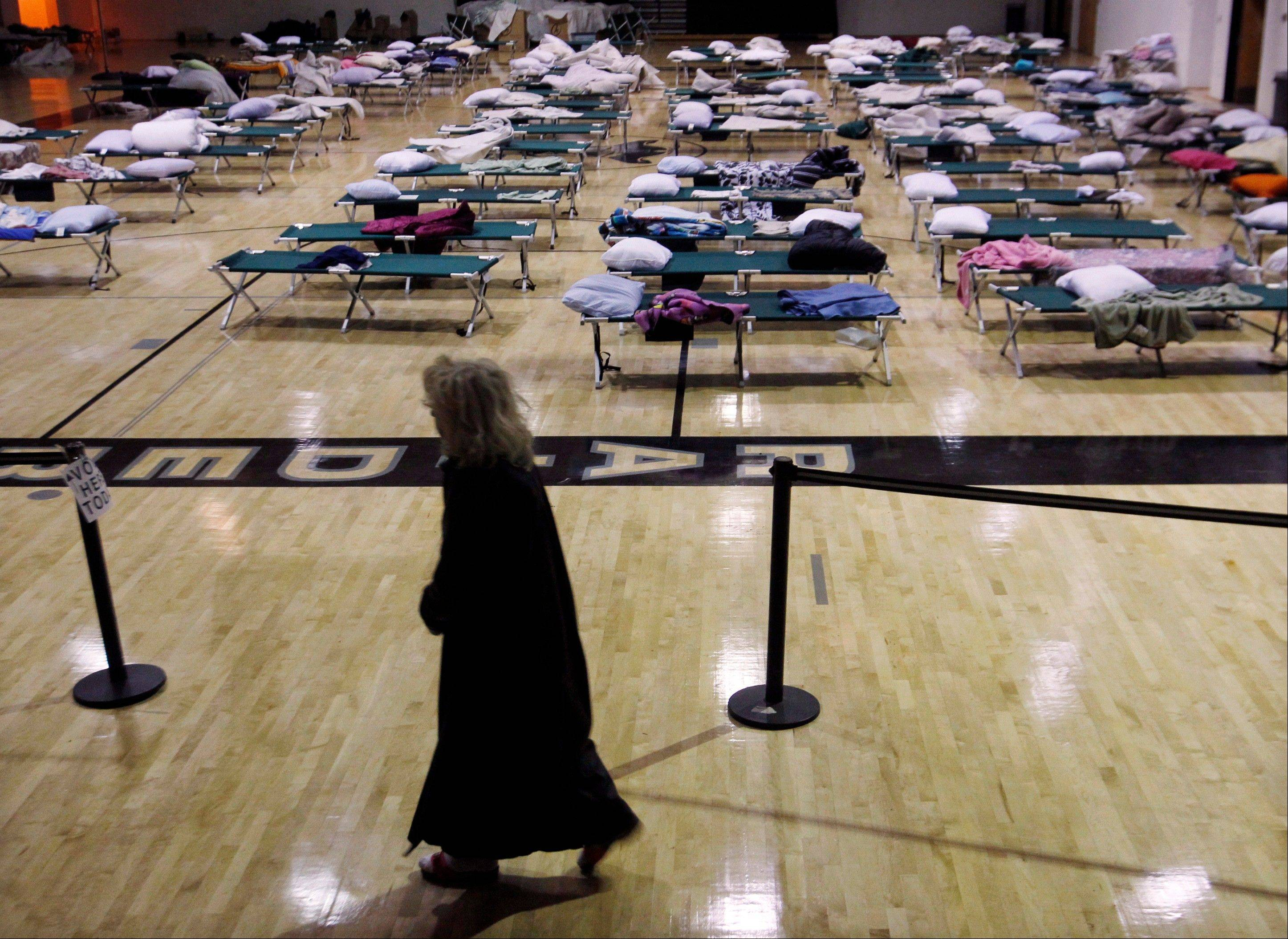 A person walks through a makeshift shelter in a gymnasium at Toms River East High School as they arrive to vote Tuesday, Nov. 6, 2012, in Toms River, N.J. N.J. Voter turnout was heavy in several storm-ravaged Jersey Shore towns, with many voters expressing relief and even elation at being able to vote at all, considering the devastation.