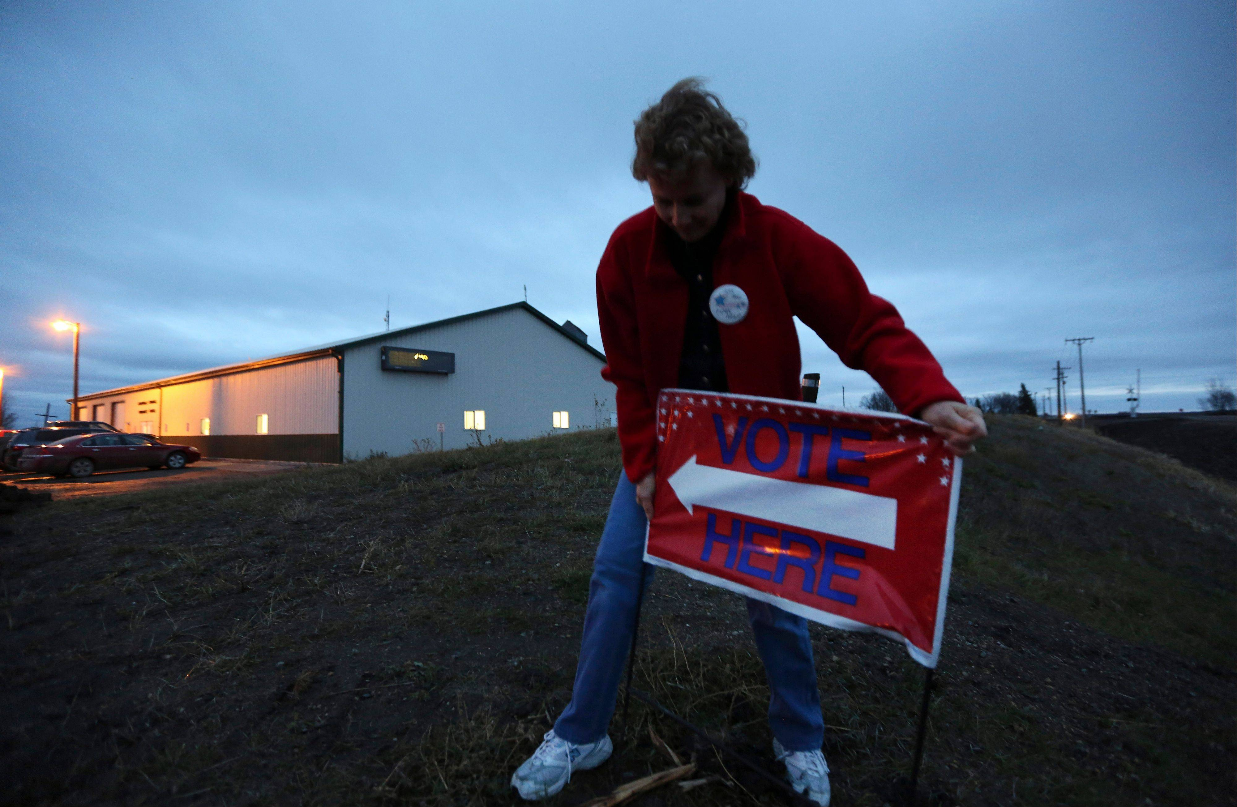 "Election Judge Victoria Colwell places a ""vote here"" sign in the ground in front of the Argusville Firehall Community Center in rural Cass County just before the polls open on Election Day in Argusville, N.D., Tuesday, Nov. 6, 2012."