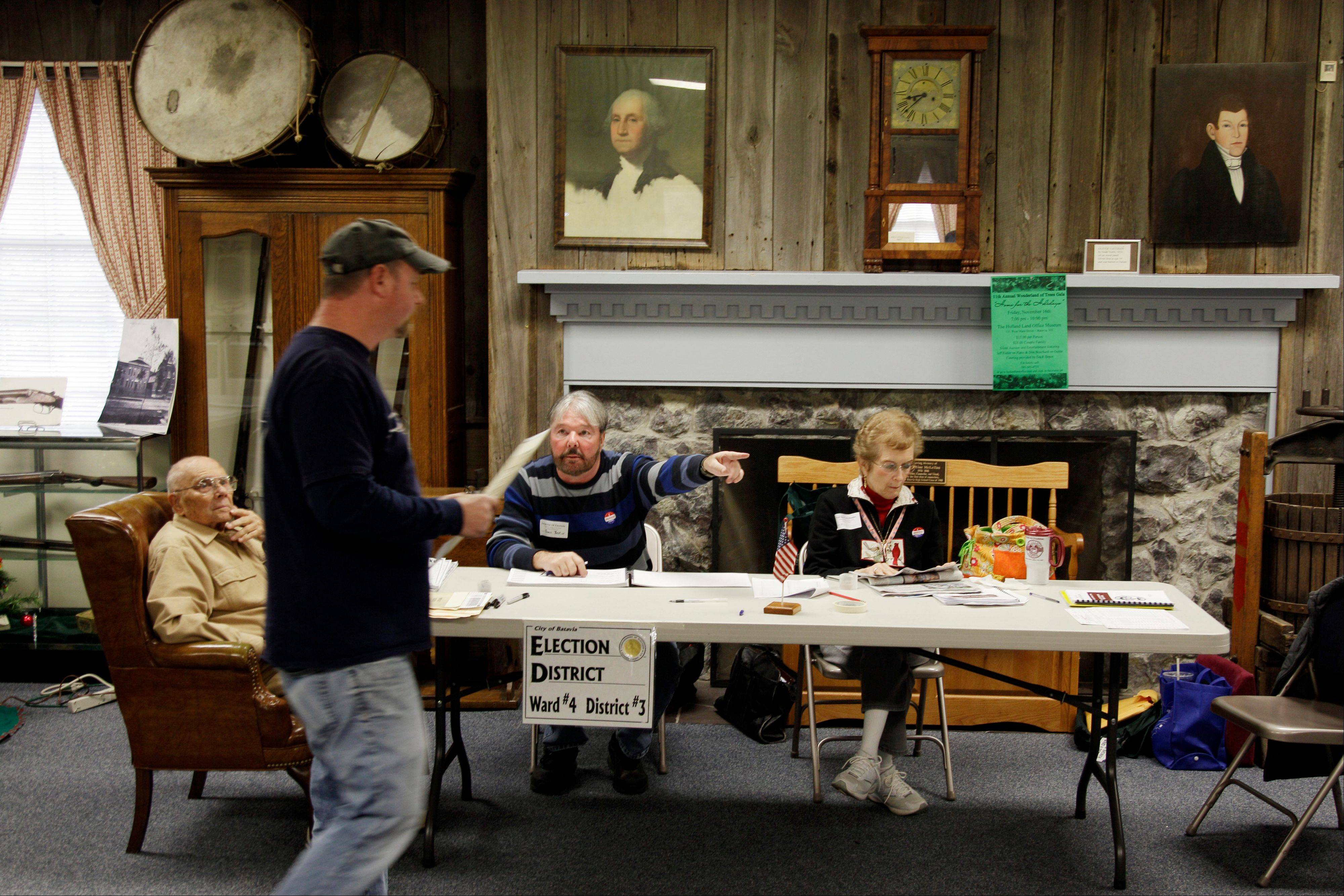 Polling Site Inspector James Bestine points out the ballot box to a voter on Election Day at the Holland Land Office Museum in Batavia, N.Y., Tuesday, Nov. 6, 2012.