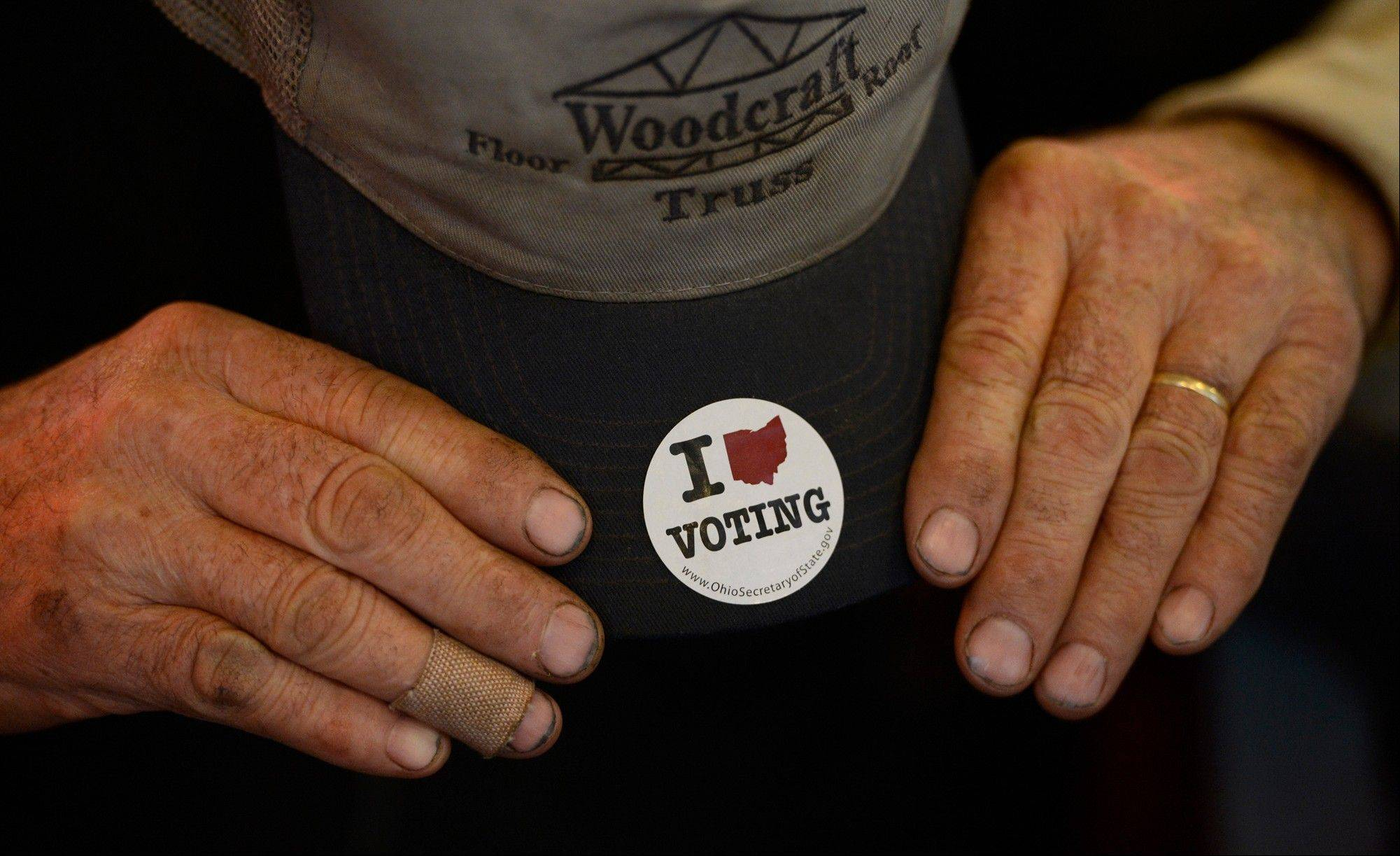 The hands of Sam Martin are seen with a sticker he received after voting early last week, as he gathers with others on Election Day for breakfast in the Nutcracker Restaurant, a 50s style diner, Tuesday, Nov. 6, 2012, in Pataskala, Ohio.