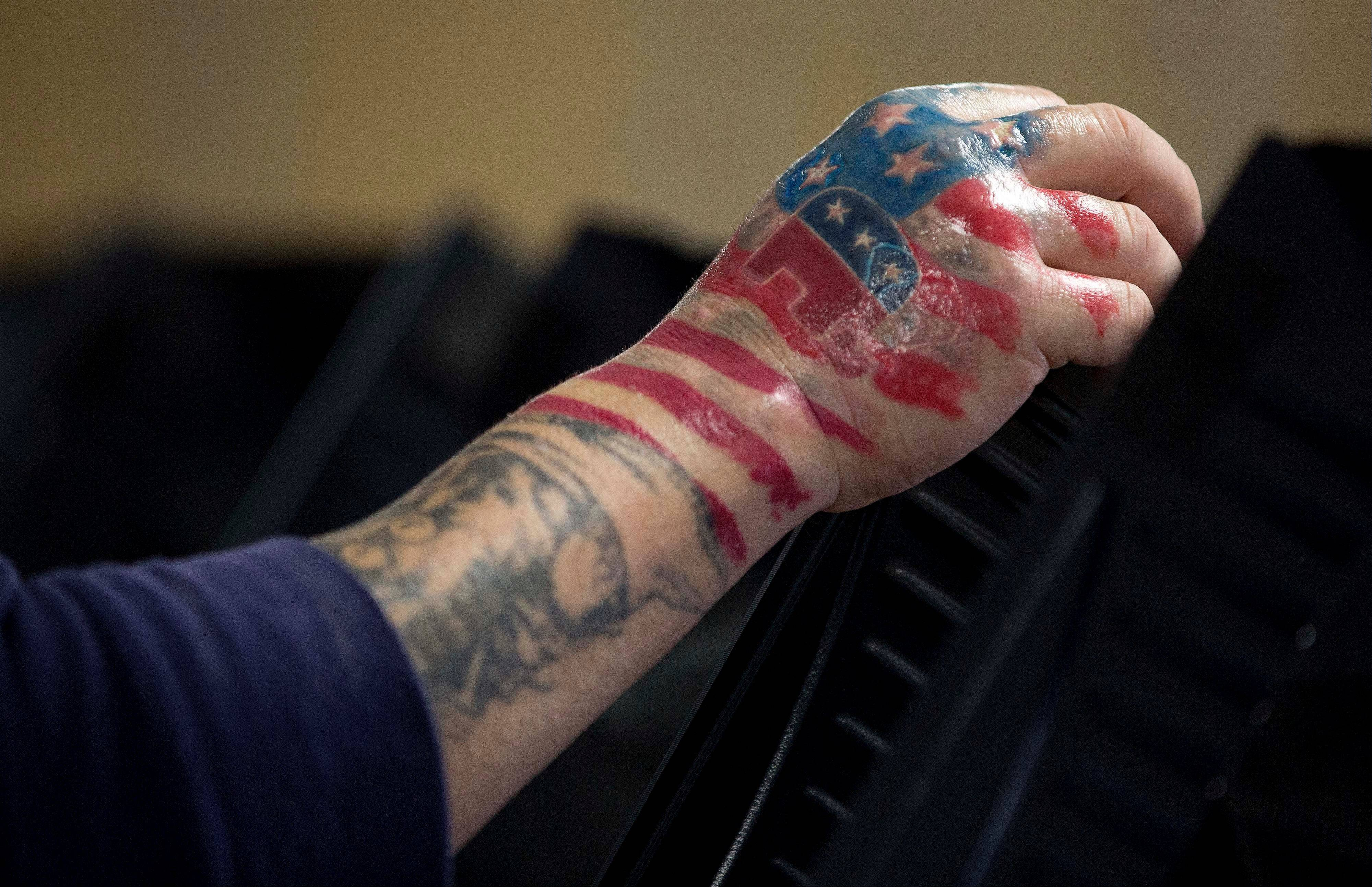 "A new tattoo showing his choice of political party is seen on the right hand of Victor ""The Snake Mann"" Wolder as he votes on Election Day, Tuesday, Nov. 6, 2012, in Las Vegas."