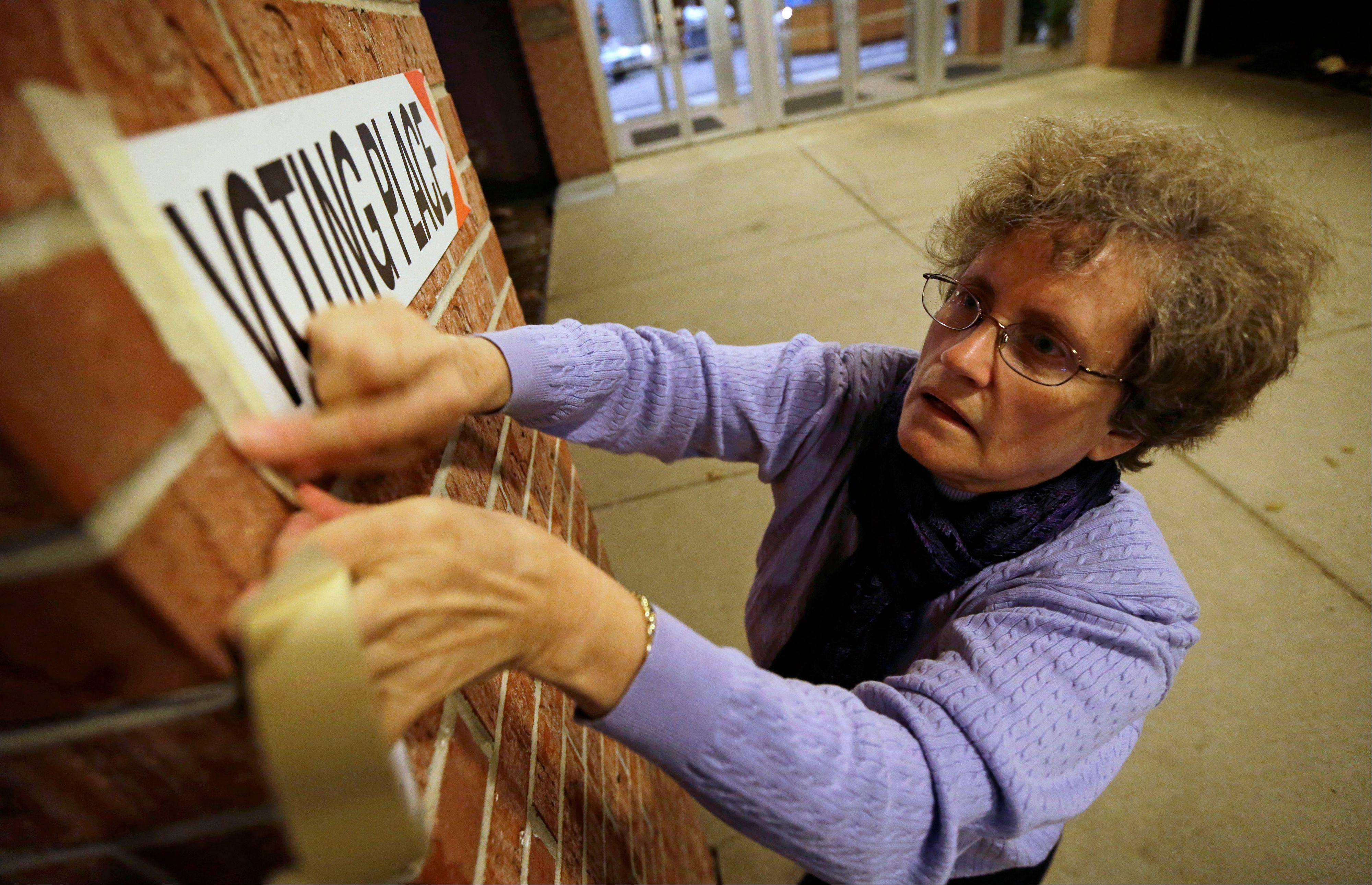 Poll worker Linda Blair hangs a sign before opening Precinct 39 up to allow voters to cast their ballots on Election Day, Tuesday, Nov. 6, 2012, at the First Church of the Open Bible in Des Moines, Iowa.