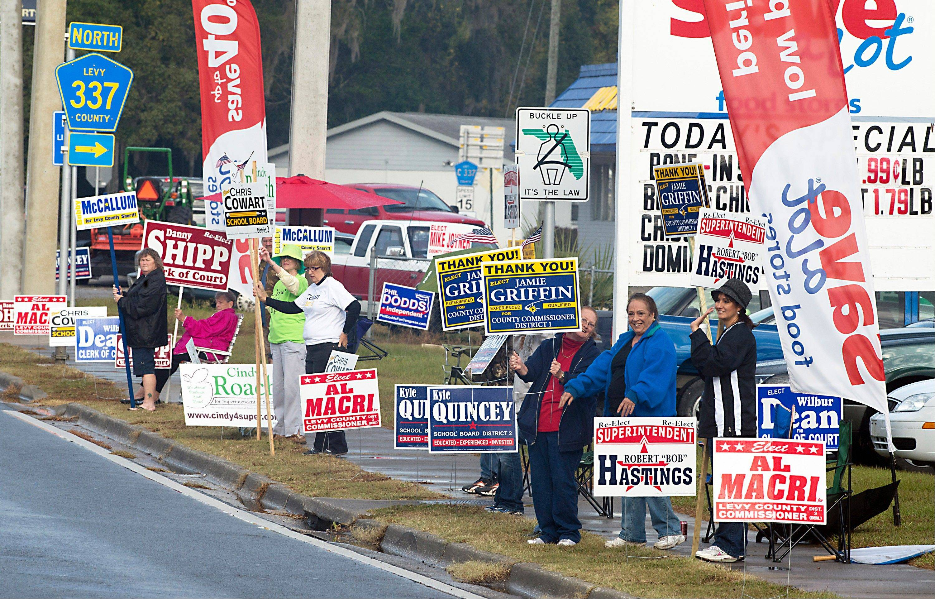 Friends and campaign workers line the highway across from the voting headquarters in Bronson, Fla., Tuesday, Nov. 6, 2012. Despite the national interest in the presidential race, there are no presidential campaign signs urging voters to pick those candidates.