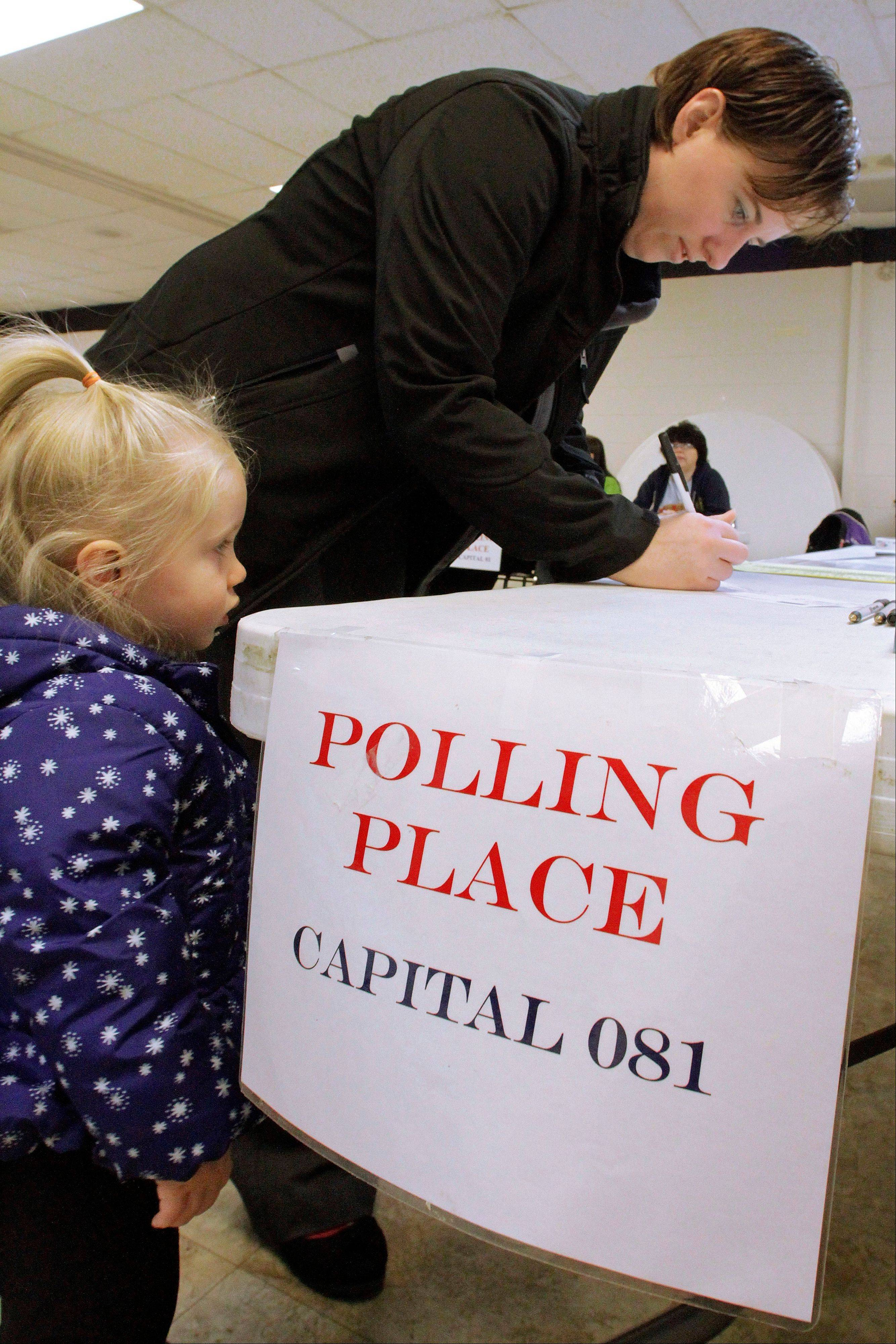 With her daughter, Katrina, 2, looking on, Pamela Clapp votes on election day Tuesday, Nov. 6, 2012 in Springfield, Ill.