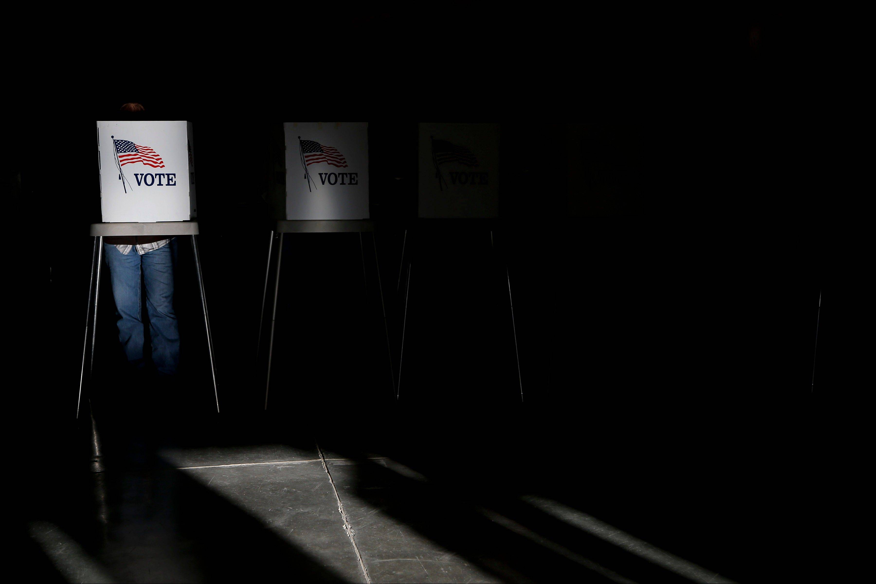 Voting booths are illuminated by sunlight as voters cast their ballots at a polling place in Billings, Mont., Tuesday, Nov. 6, 2012.