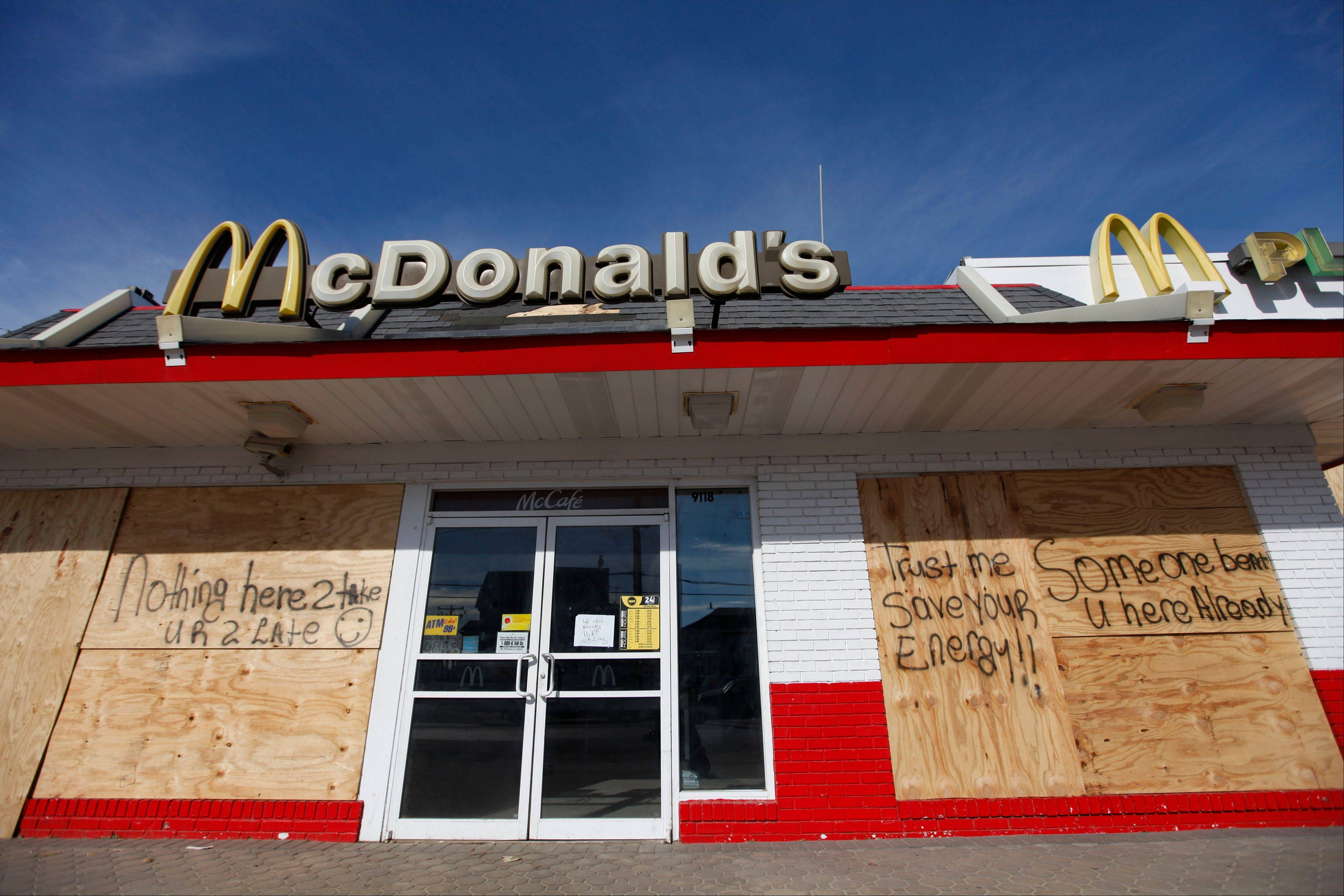 Messages discouraging looters appear on a boarded-up restaurant Tuesday in the Queens borough of New York.