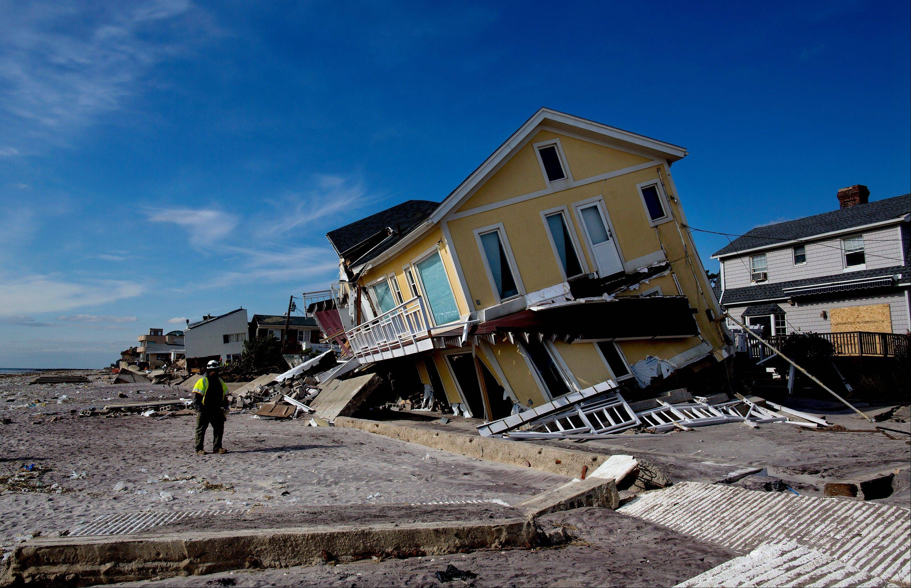 A damaged home tilts to one side along the beach in the Belle Harbor section of the borough of Queens, New York, in the wake of Superstorm Sandy on Monday. A coastal storm that threatens to complicate the Superstorm Sandy cleanup efforts now looks like it will be weaker than expected, experts say.