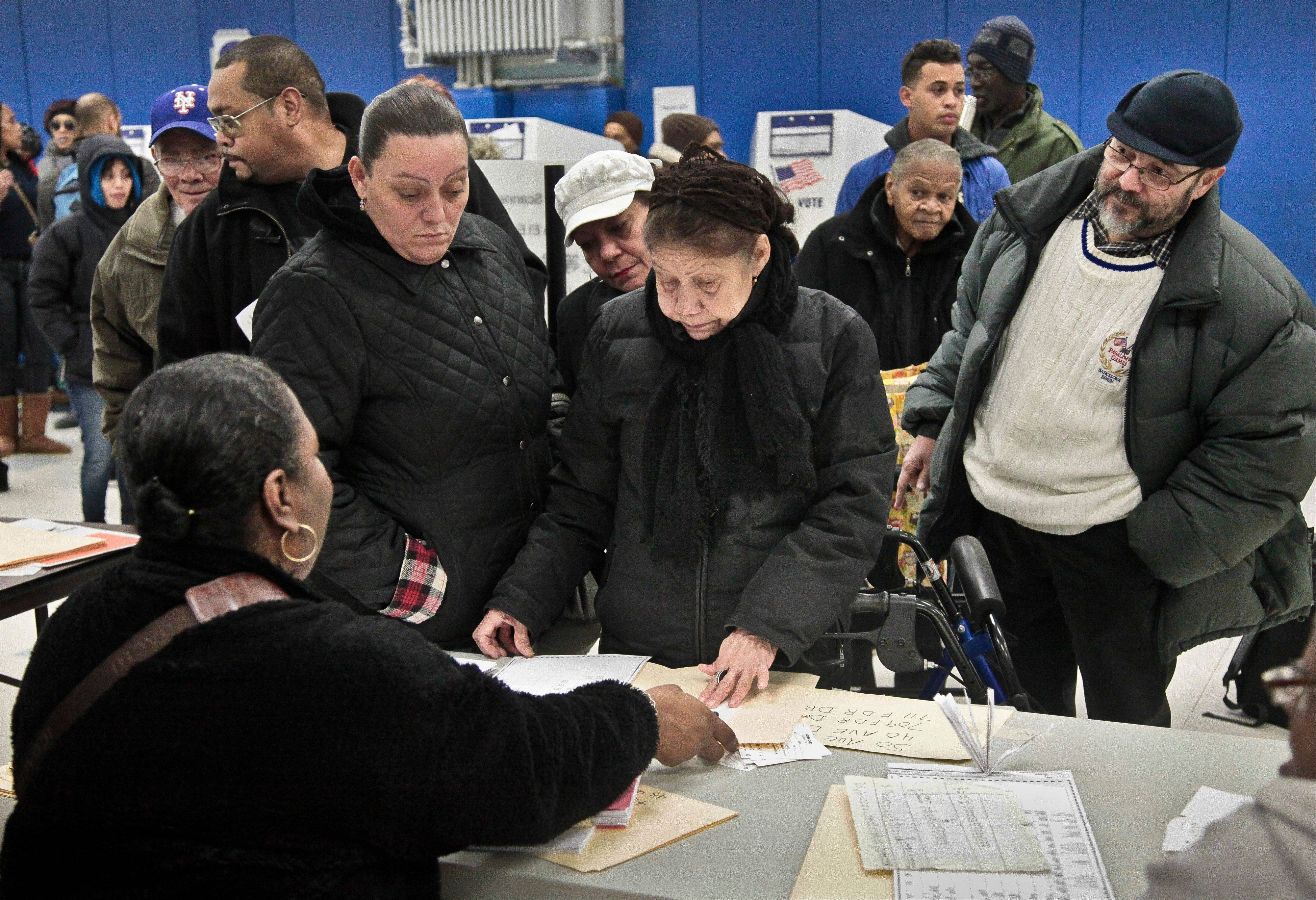A poll worker, seated left, gives instructions to voters arriving from a relocated polling site that closed after flooding from Superstorm Sandy, on Tuesday, Nov. 6, 2012 at P.S. 188 on Manhattan's Lower East Side, New York.