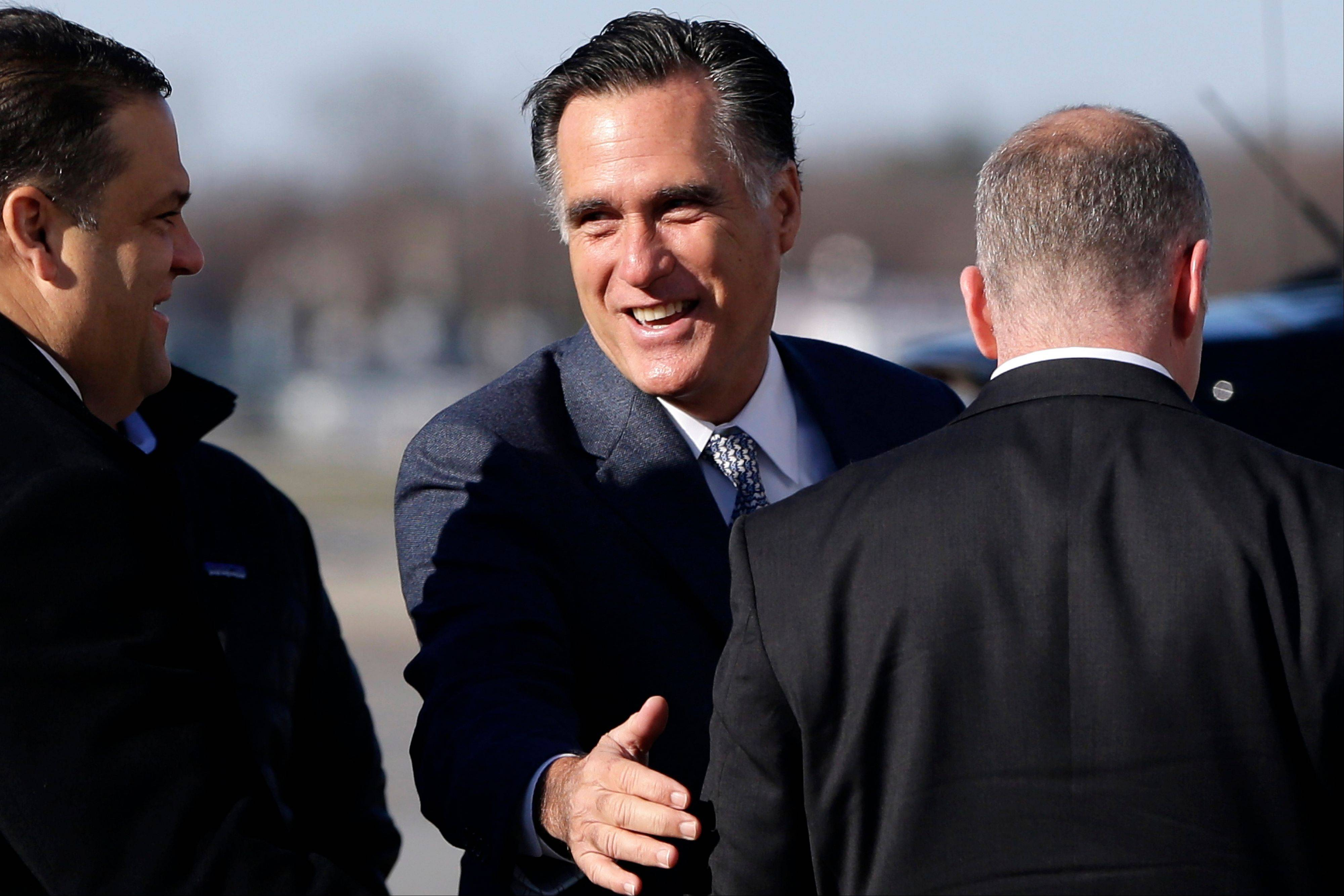 Republican presidential candidate, former Massachusetts Gov. Mitt Romney smiles as he speaks to a U.S. Secret Service agent before boarding his plane in Bedford Mass., for Cleveland, Ohio, Tuesday, Nov. 6, 2012.