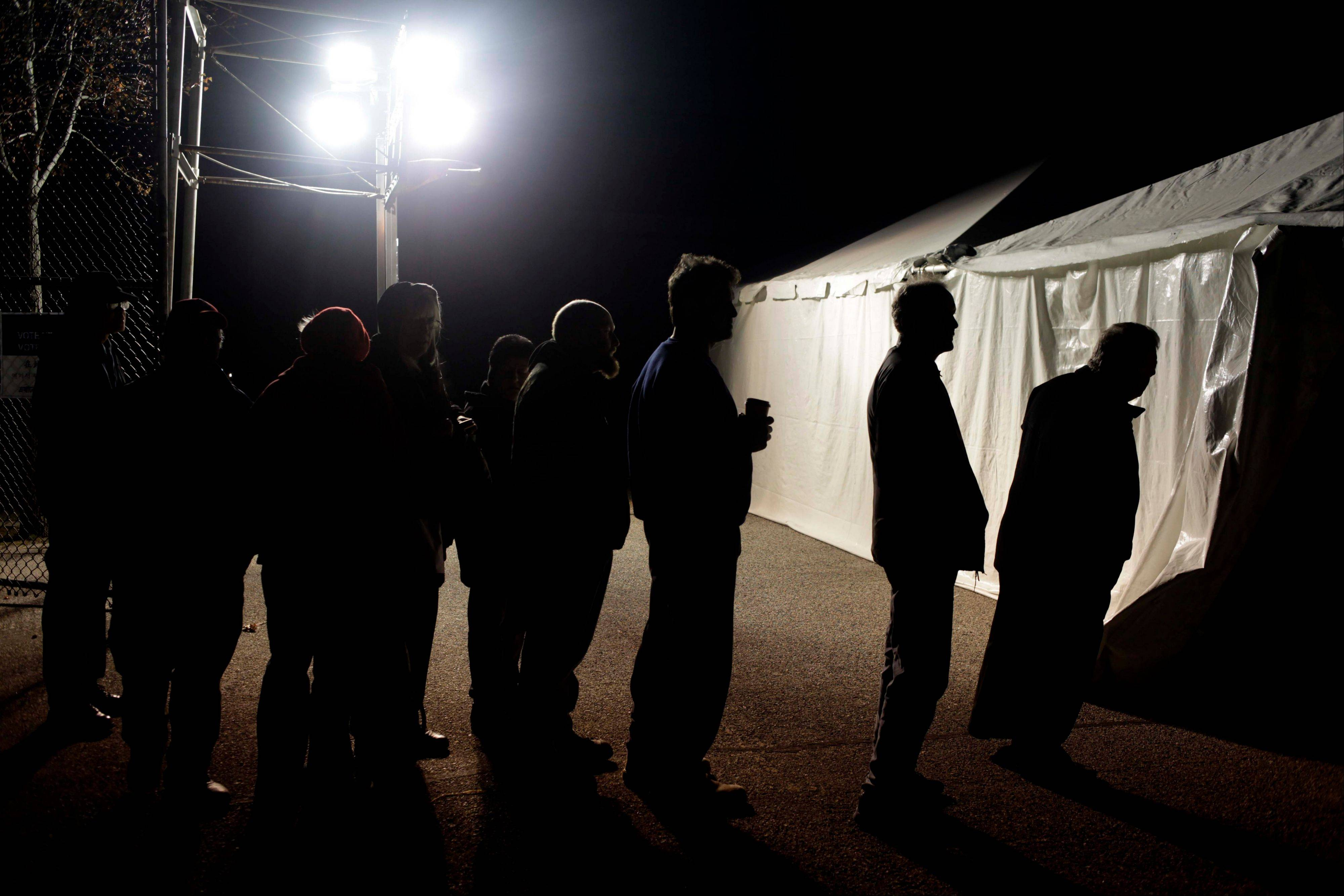 Under the lights of a generator, voters wait in line outside of a tent serving as a polling site in the Midland Beach section of Staten Island, New York, on Election Day Tuesday, Nov. 6, 2012. The original polling site, a school, was damaged by Superstorm Sandy.