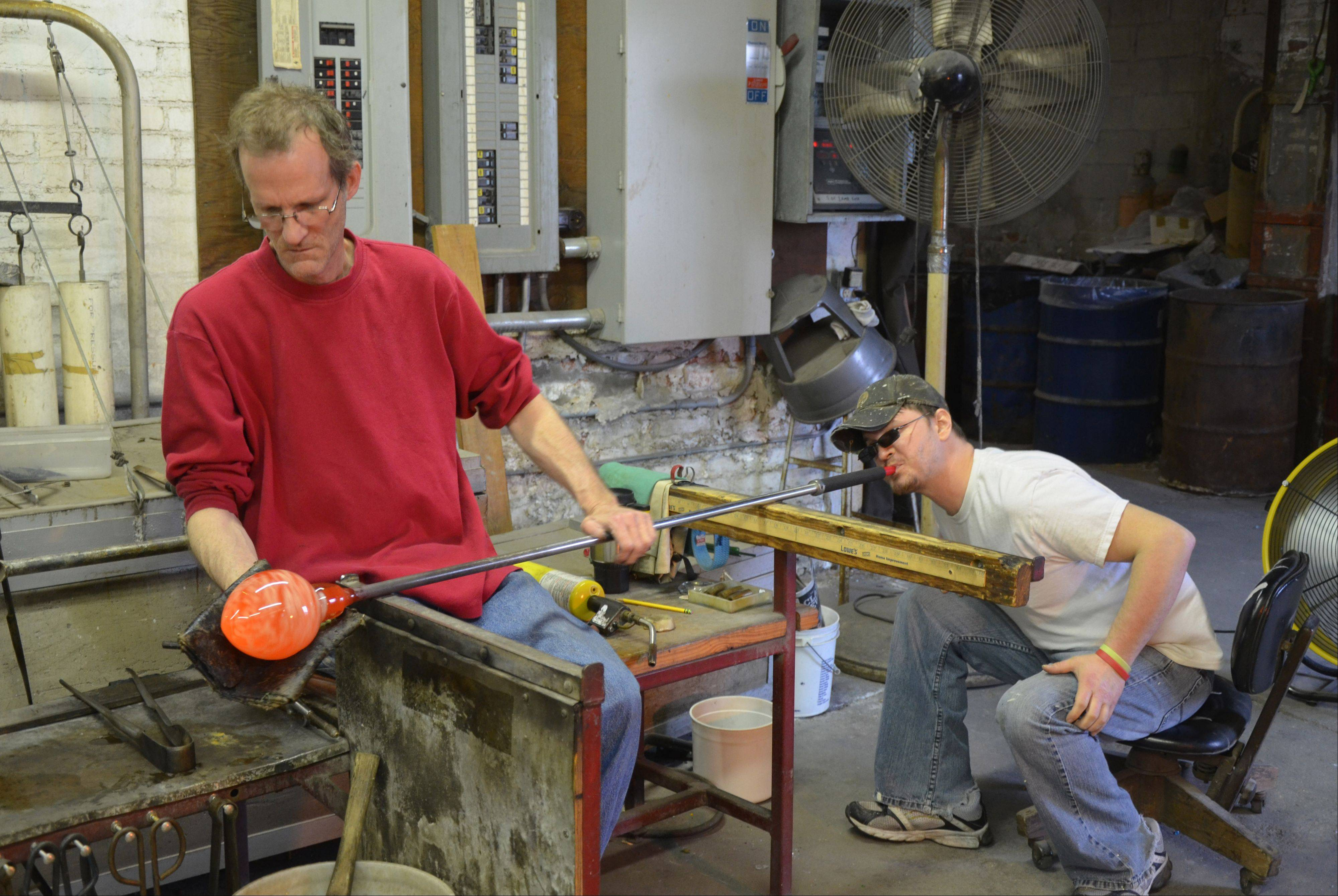 Workers at Kokomo Opalescent Glass create pendant lights by heating and shaping the molten glass mixture.