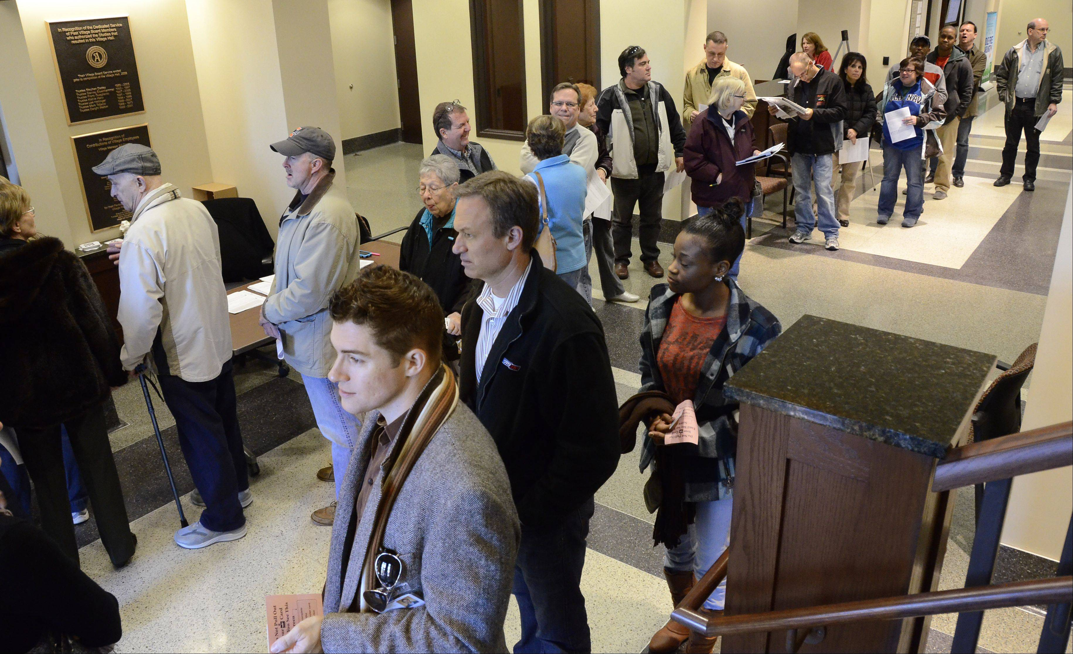 Voters line up Friday at Arlington Heights village hall. Record numbers of people voted early in the suburbs, which could ease your wait today.