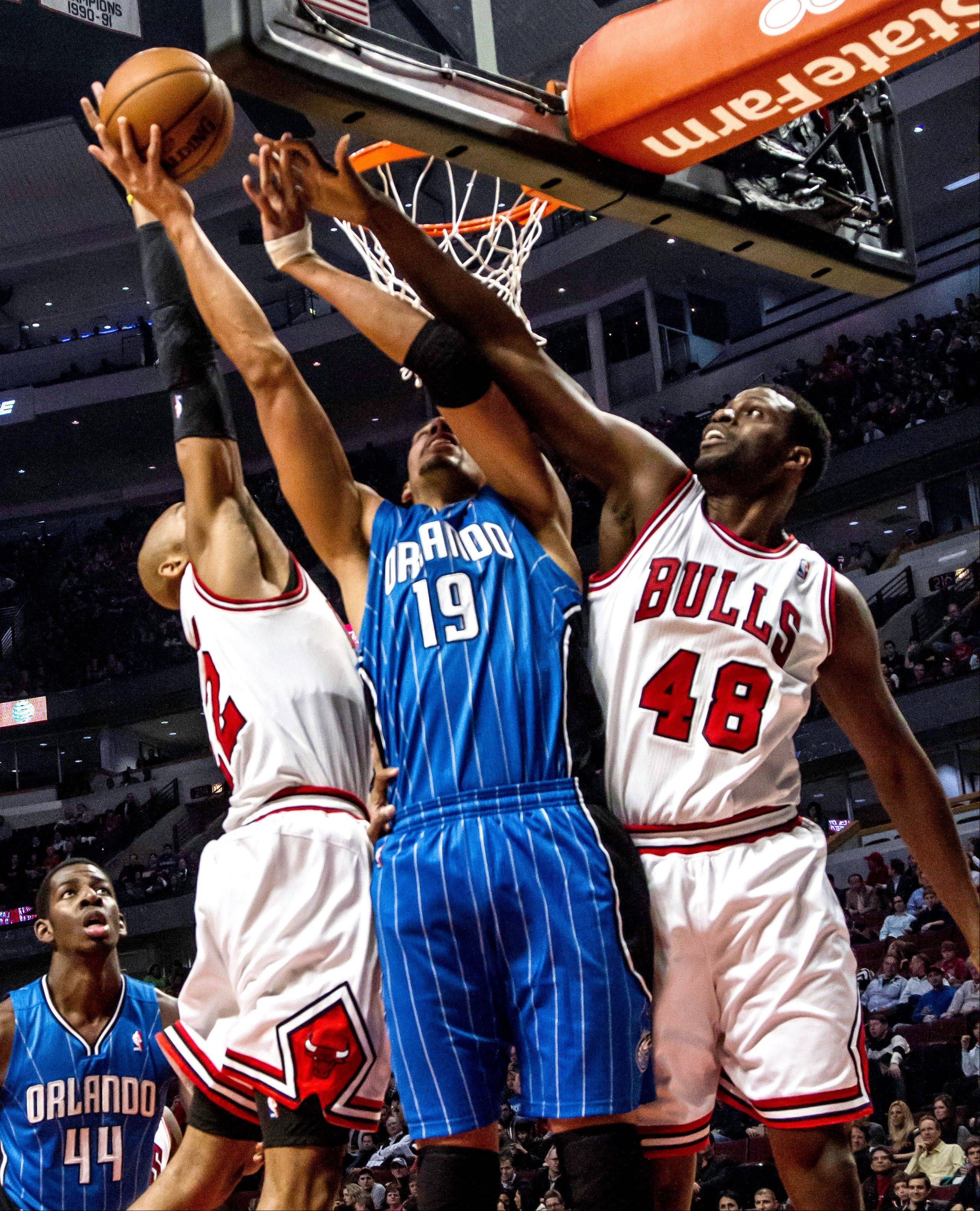 The Bulls' Taj Gibson (22) and Nazr Mohammed (48) put defensive pressure on Orlando's Gustavo Avon.
