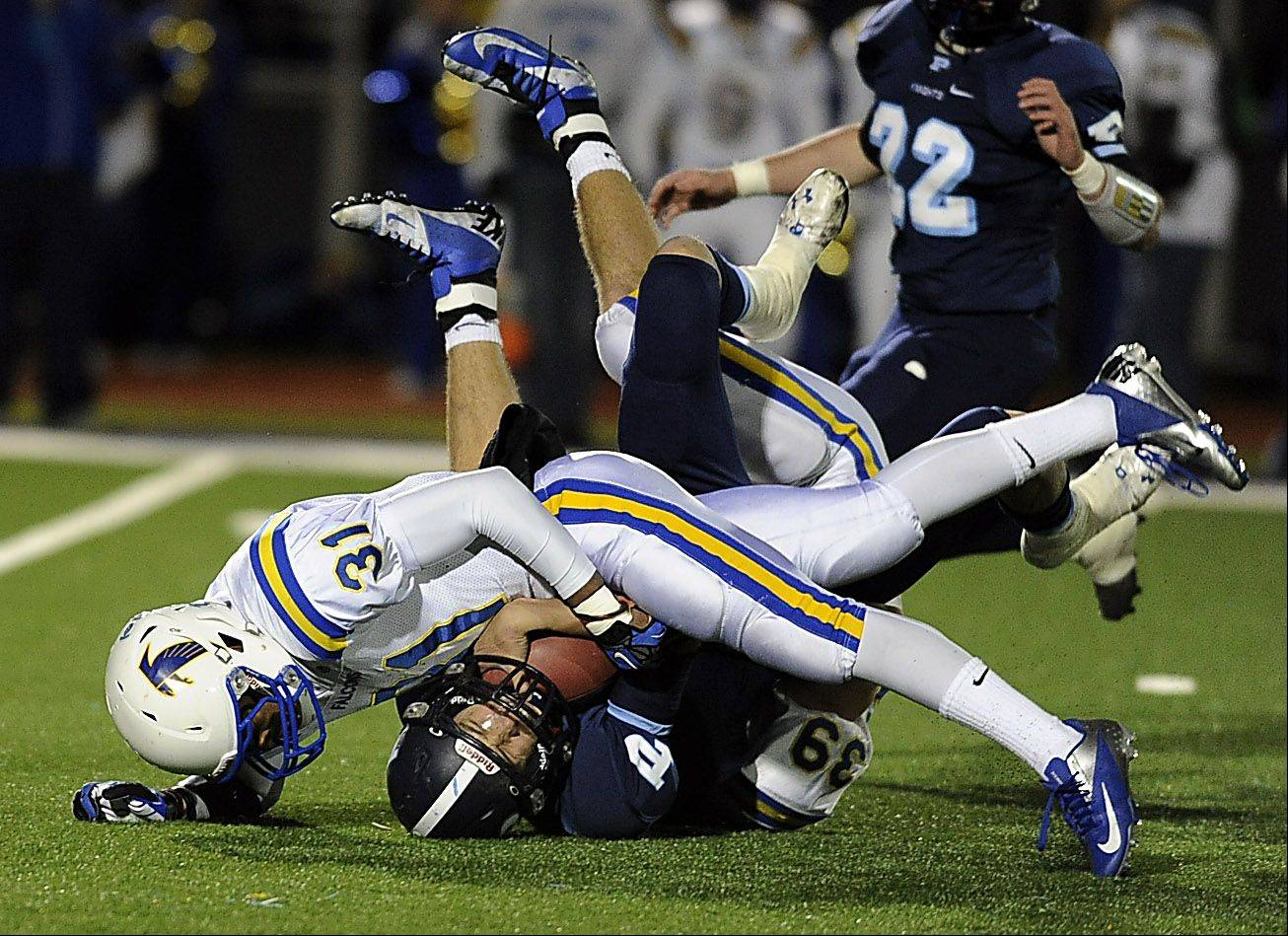 Wheaton North's Jaylen Howze and Kellen Cleveland bring down Prospect's quarterback Devin O'Hara in the Class 7A second-round football game at Prospect High School on Friday.