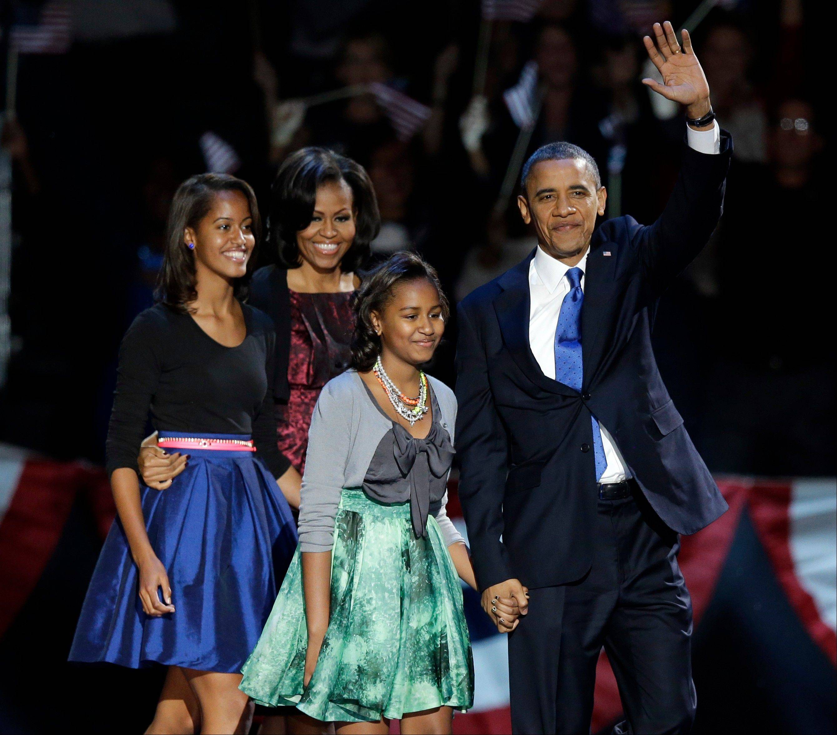 President Barack Obama waves as he walks onstage with first lady Michelle Obama and daughters Malia and Sasha at his election night party Wednesday in Chicago.