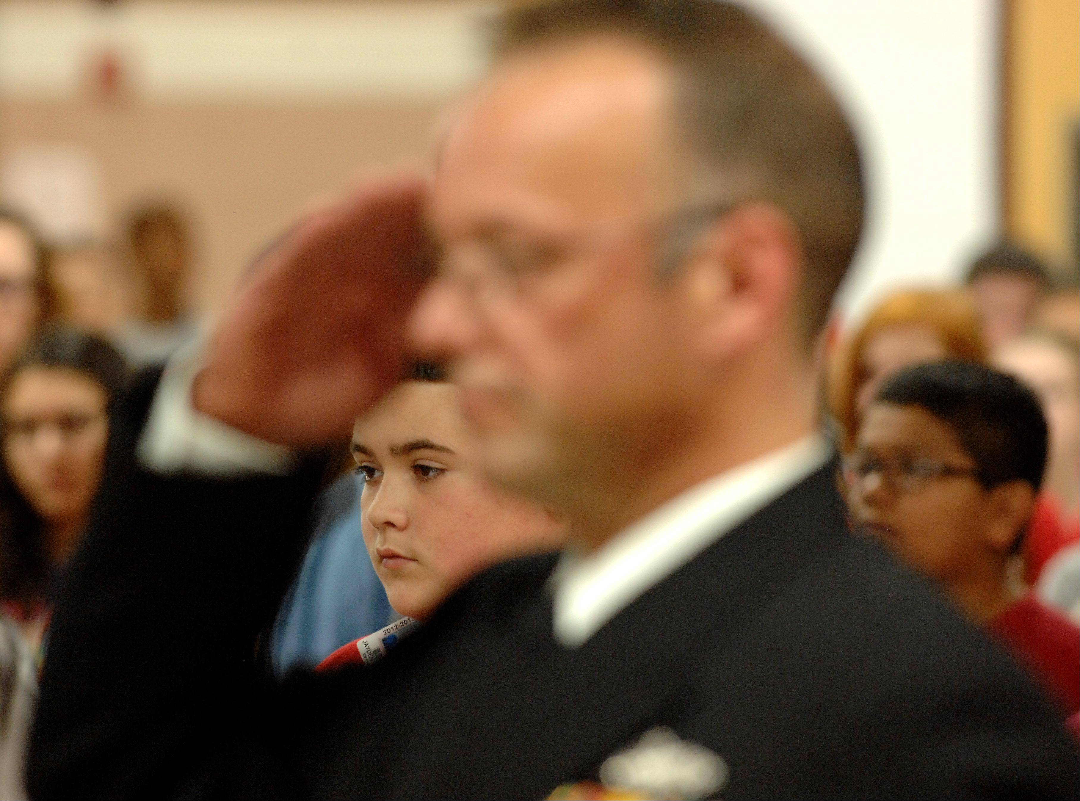 Seventh-grader Jayden Vento is framed by the salute of retired Navy Chief Petty Officer Dan Coakley as the national anthem plays during Jewel Middle School's seventh annual Veterans Day assembly Wednesday at the school in North Aurora.