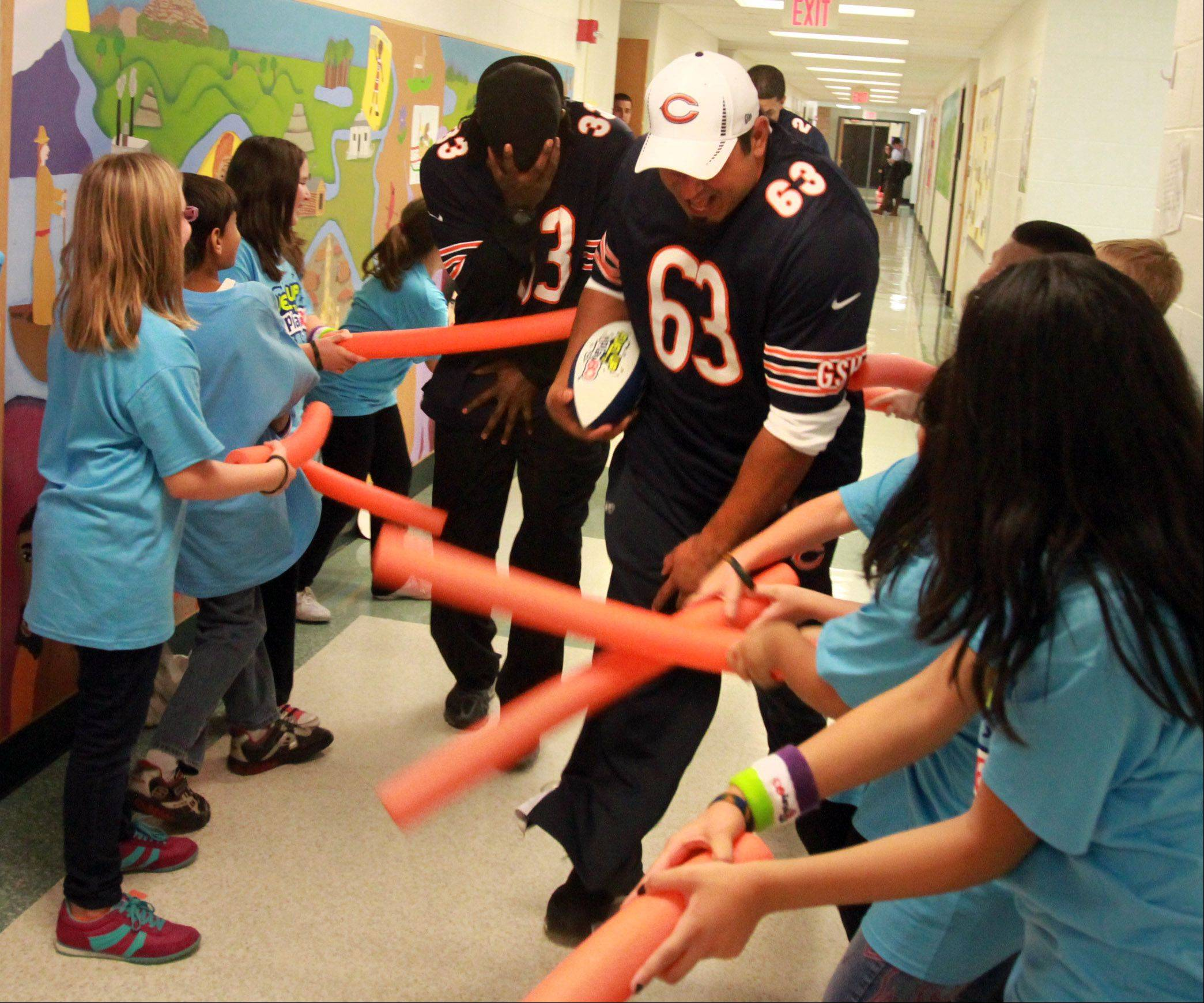 "Roberto Garza, left, and ""Peanut"" Tillman rush down through a hallway at Ridge Family Center for Learning as students try to catch them with foam tubes."