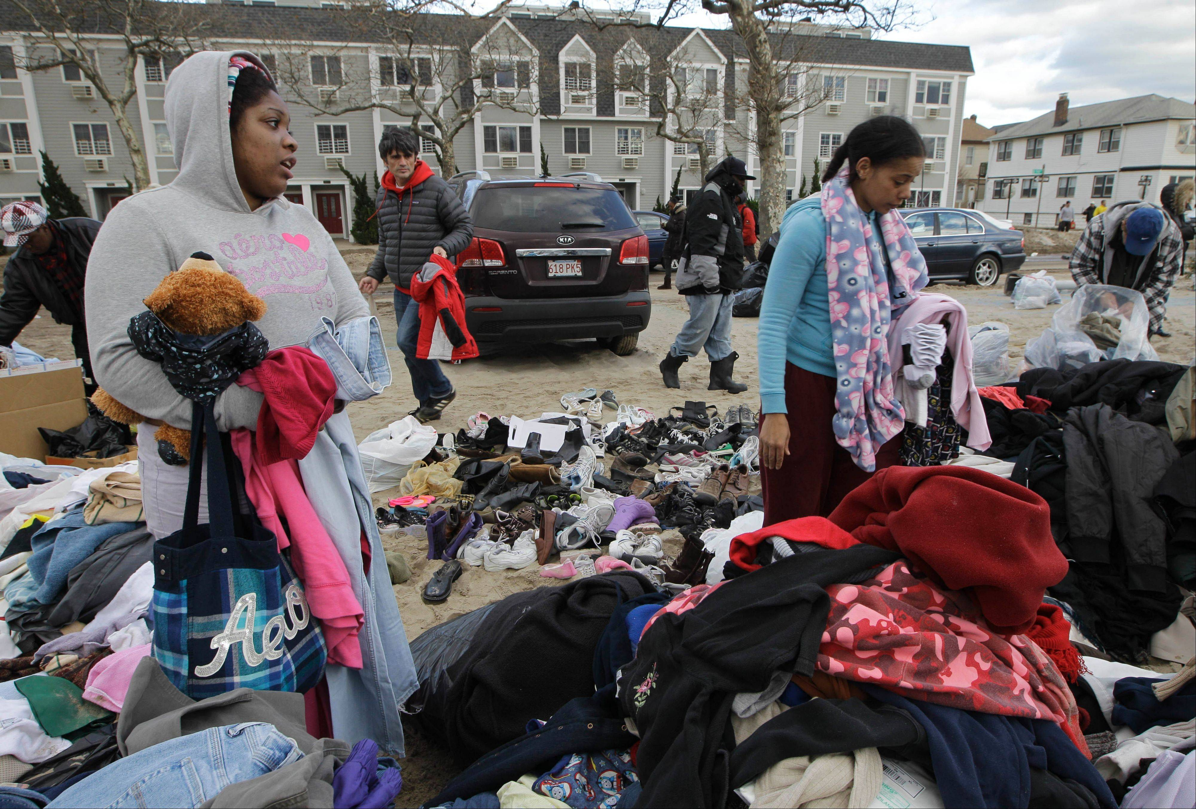Mecca Traynham, left, and Elena Richardson, right, comb through donated warm and clean clothes, children's toys, and blankets at a distribution point in the Rockaways, a neighborhood that was hit hard and is still without power in the wake of Superstorm Sandy, Saturday, Nov. 3, 2012, in New York.