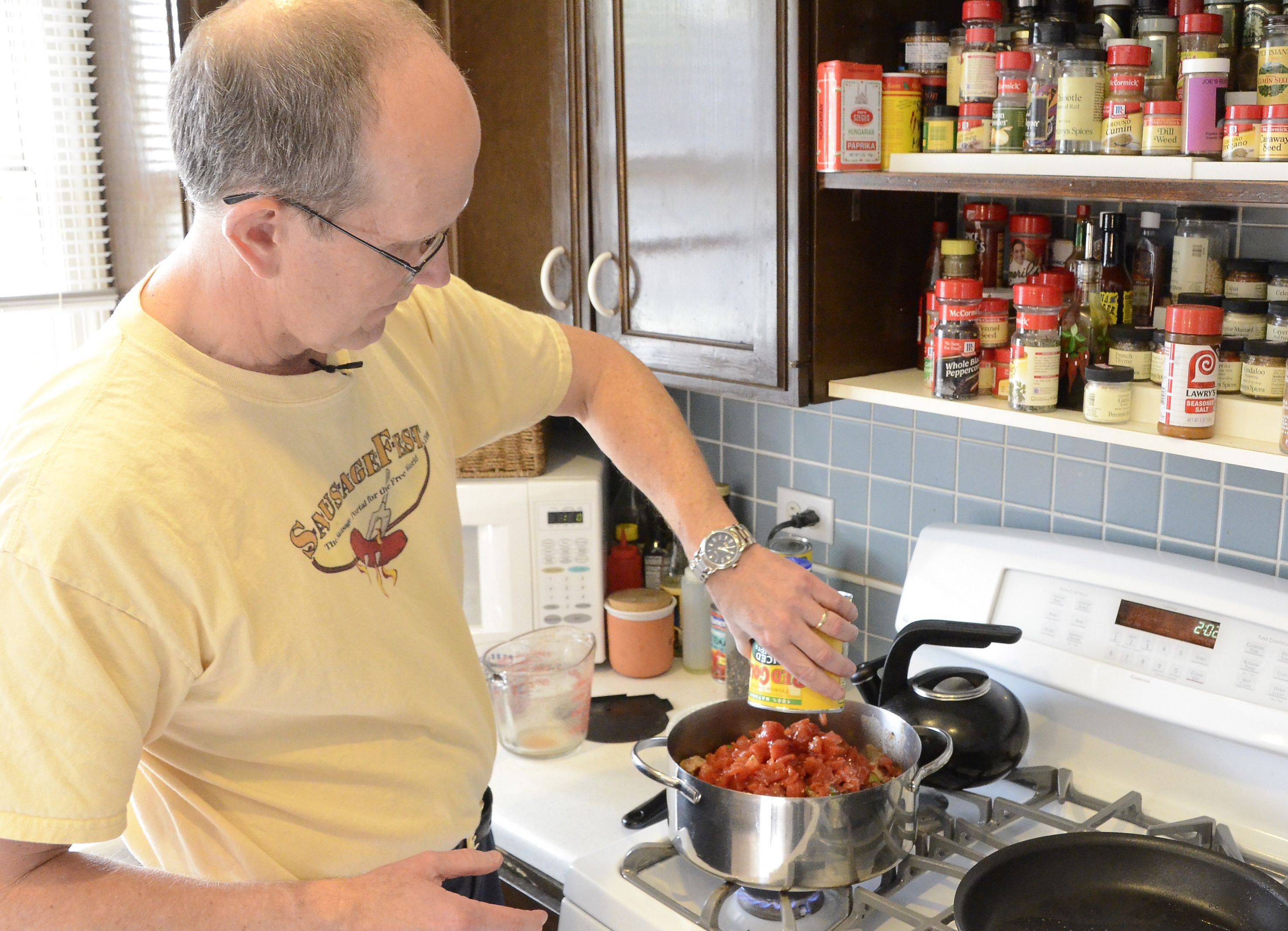 Kent Kleiva adds chopped tomatoes to his three-sausage chili. He prefers a chunkier consistency over a soupier texture.