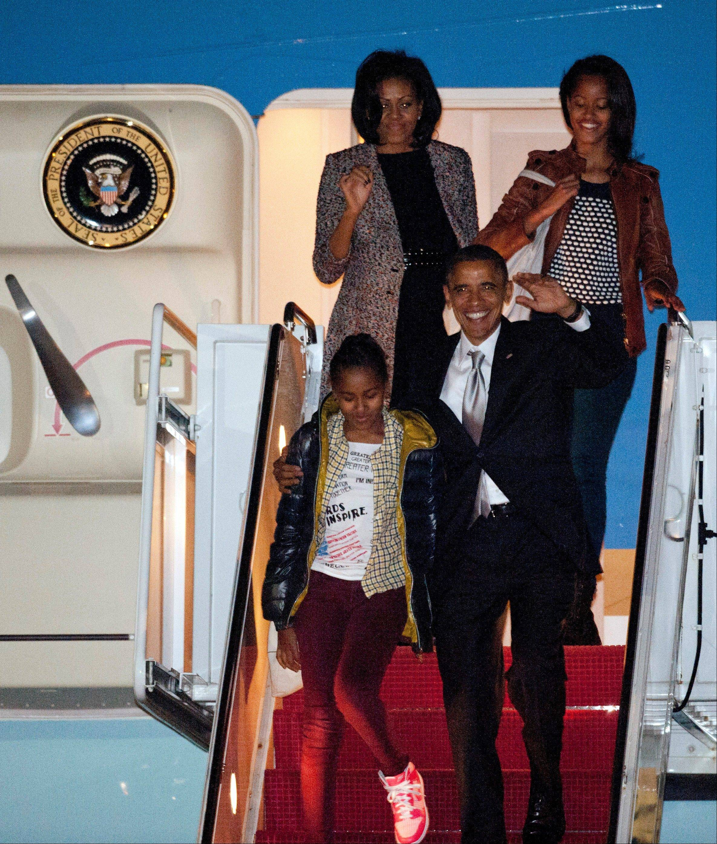President Barack Obama, with his arm around daughter Sasha, and first lady Michelle Obama and eldest daughter Malia exit Air Force One at Andrews Air Force Base, Md., after a flight from Chicago on Wednesday.