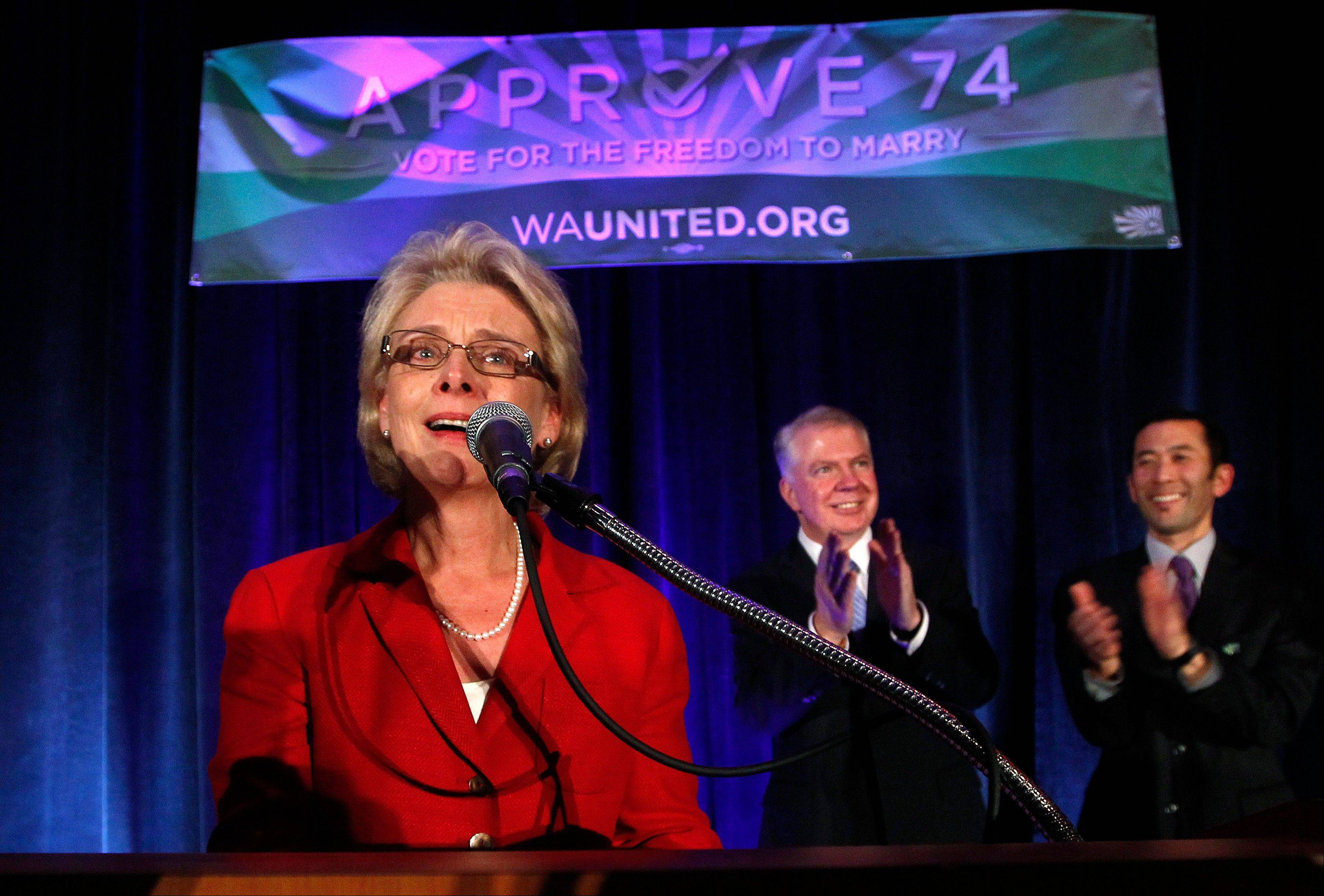 A teary-eyed Gov. Chris Gregoire, left, speaks as Sen. Ed Murray, center, and his partner Michael Shiosaki applaud behind at an election watch party for proponents of Referendum 74, which would uphold the state's new same-sex marriage law.
