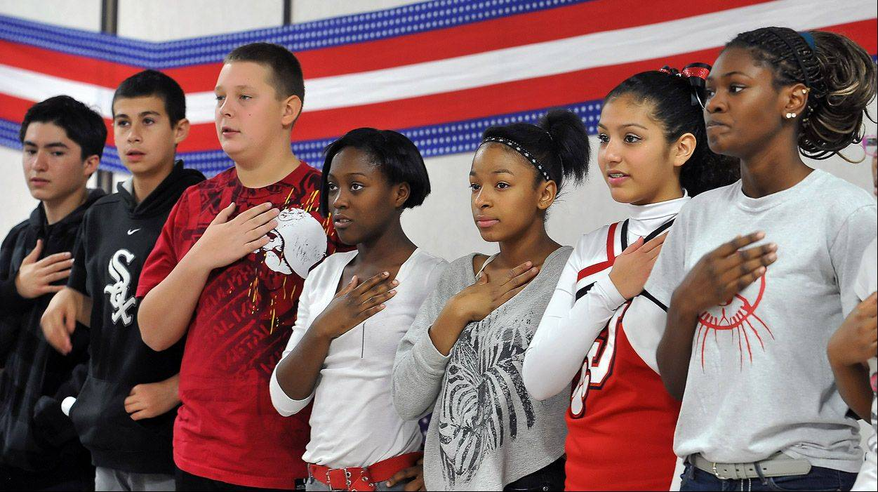 Seventh-graders recite the Pledge of Allegiance during an assembly honoring veterans Wednesday at Jewel Middle School.