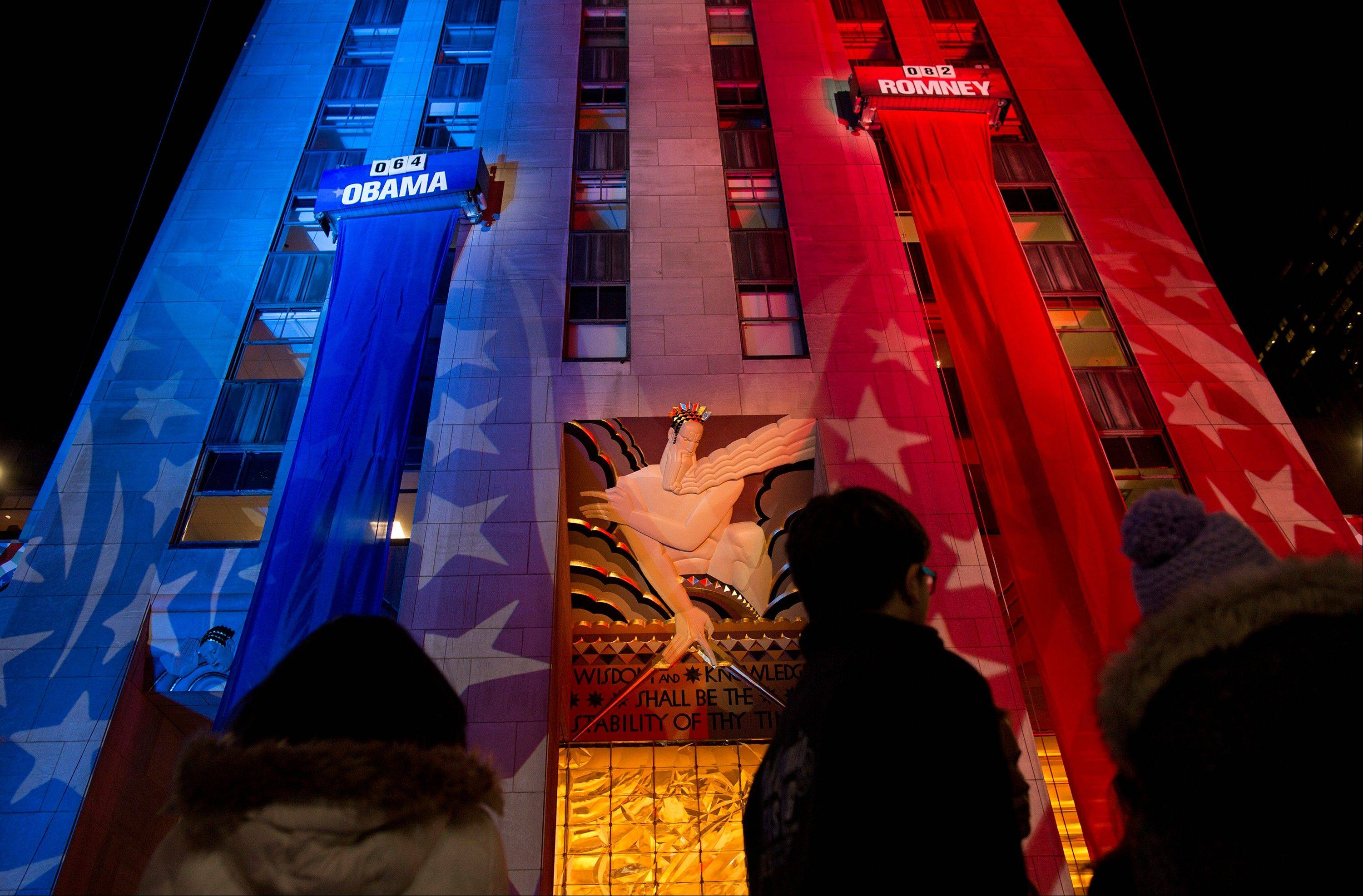 People watch early election results displayed on a utility lift suspended from the front of the GE Building at Rockefeller Center New York, Tuesday, Nov. 6, 2012.