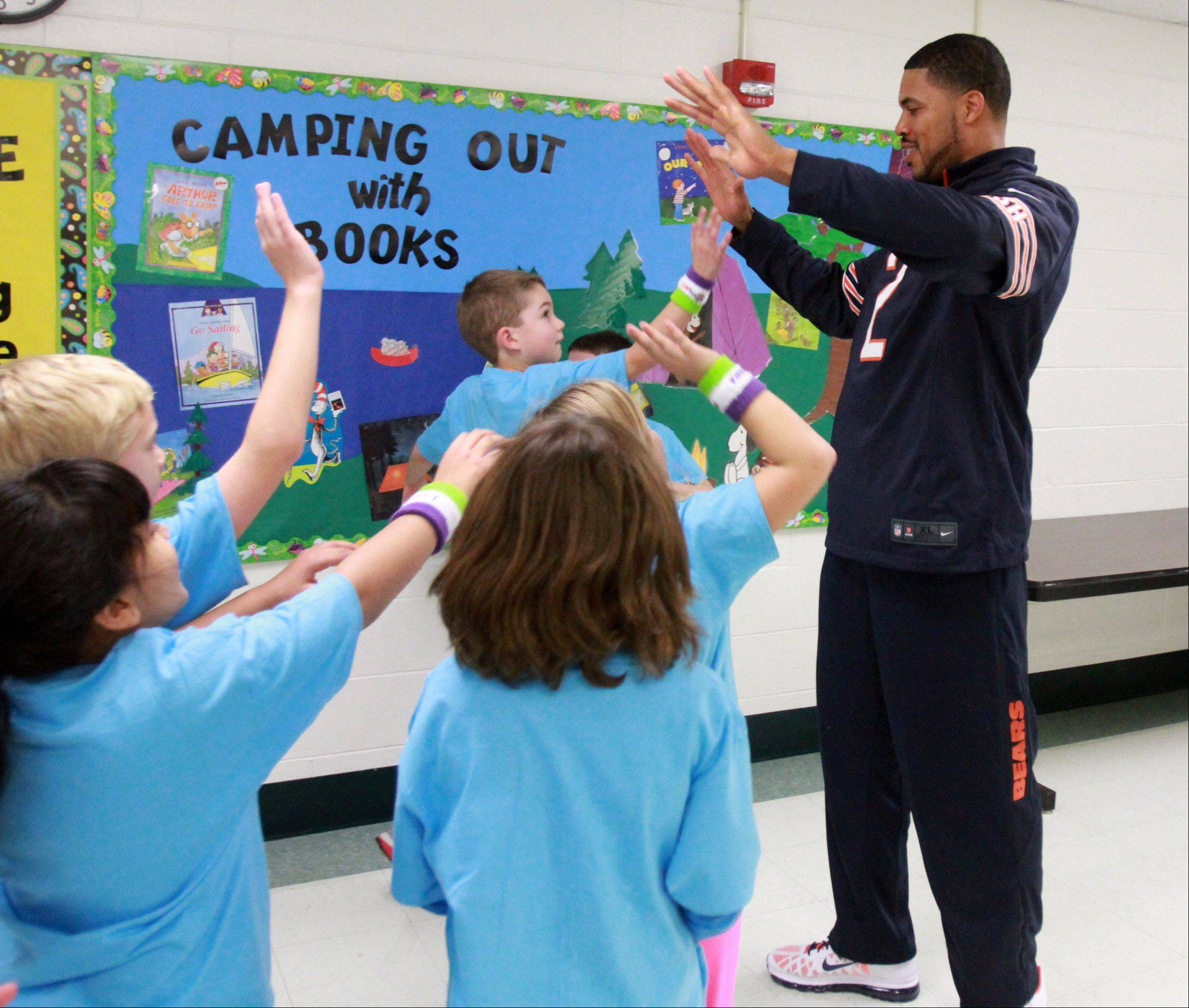 Bears quarterback Jason Campbell high-fives elementary school students at Ridge Family Center for Learning after coaching the students through push-up drills.