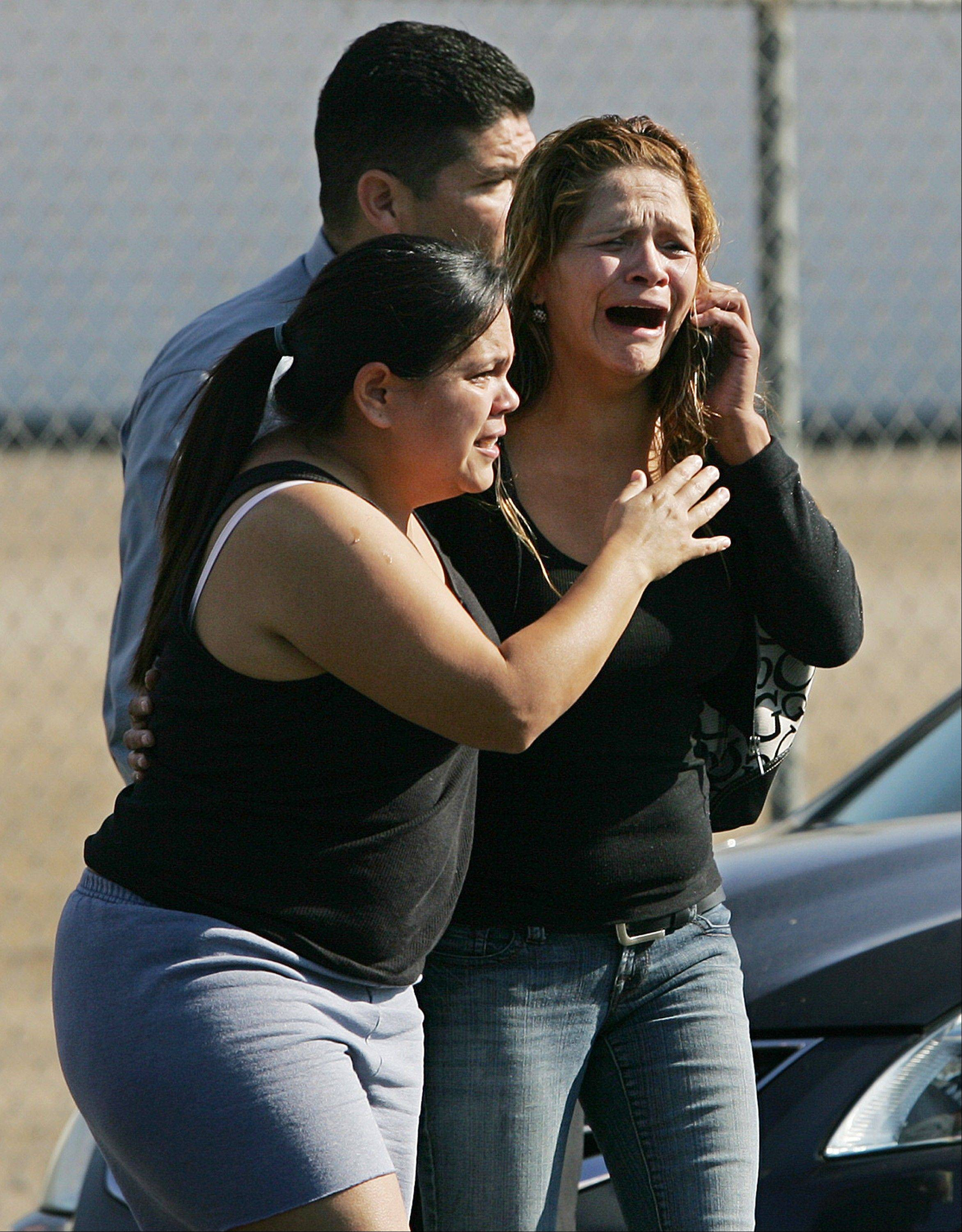 An unidentified woman cries as she's rushed into a car after learning of a workplace shooting Tuesday, Nov. 6, 2012, in Fresno, Calif. A parolee who worked at a California chicken processing plant opened fire at the business on Tuesday, killing one person and wounding three others, before shooting himself, police said.