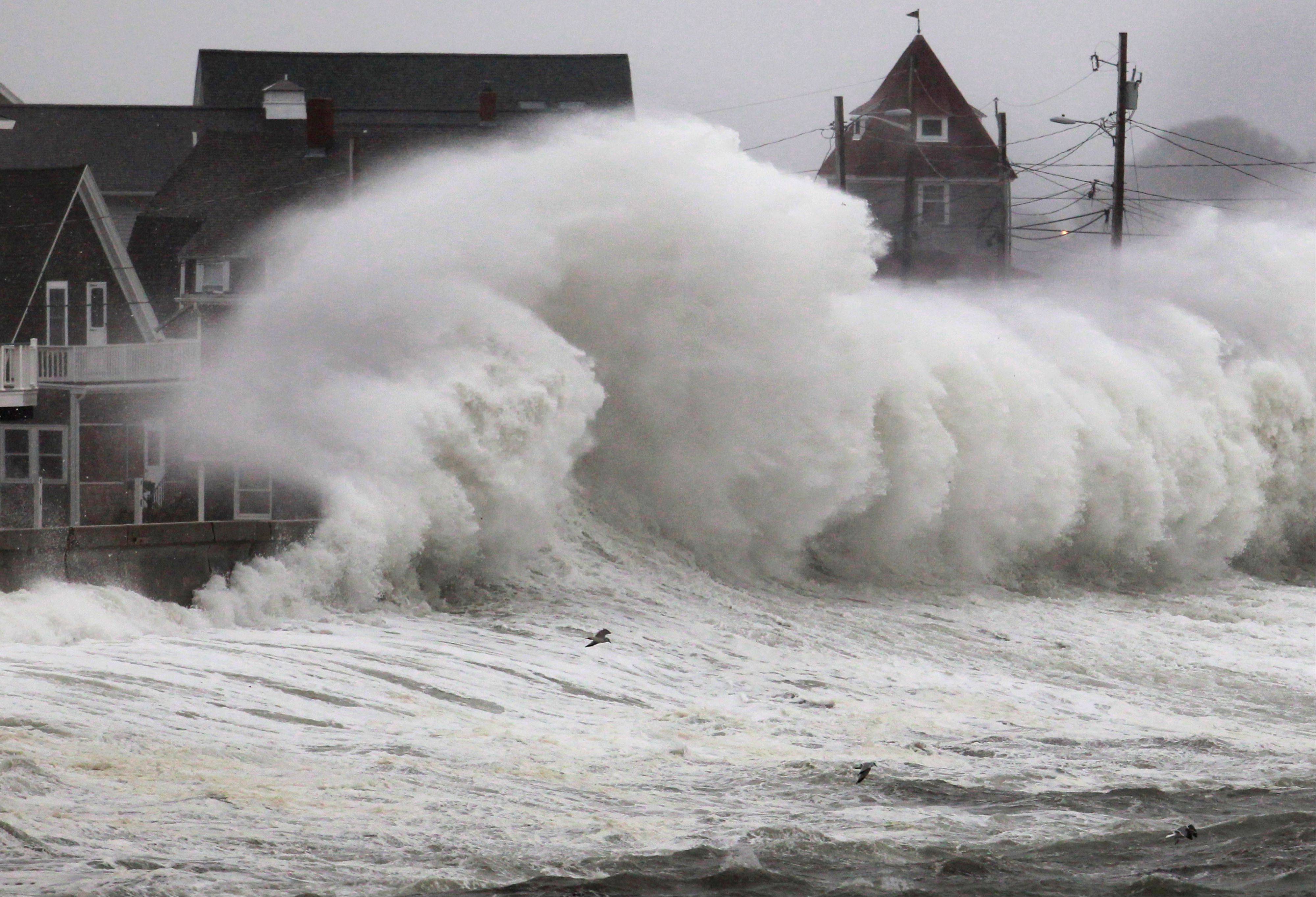 Waves crash into a seawall and buildings along the coast in Hull, Mass., Wednesday. A high-wind warning is in effect in the state until Wednesday night, with gusts of up to 60 mph expected in some costal areas, and 50 mph gusts expected for Boston and western Massachusetts.