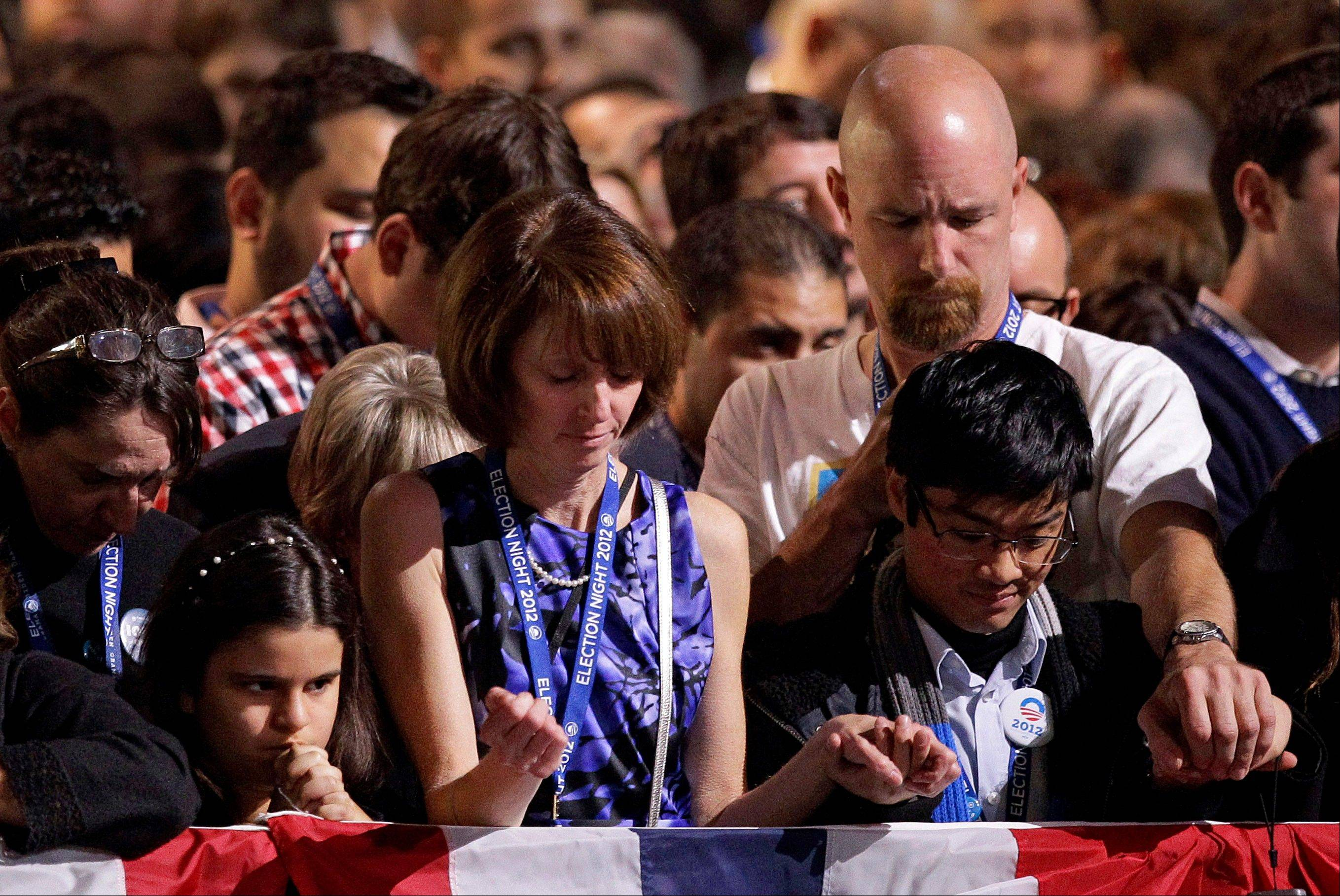 Supporters pray during the invocation at the election night party for President Barack Obama Tuesday, Nov. 6, 2012, in Chicago.