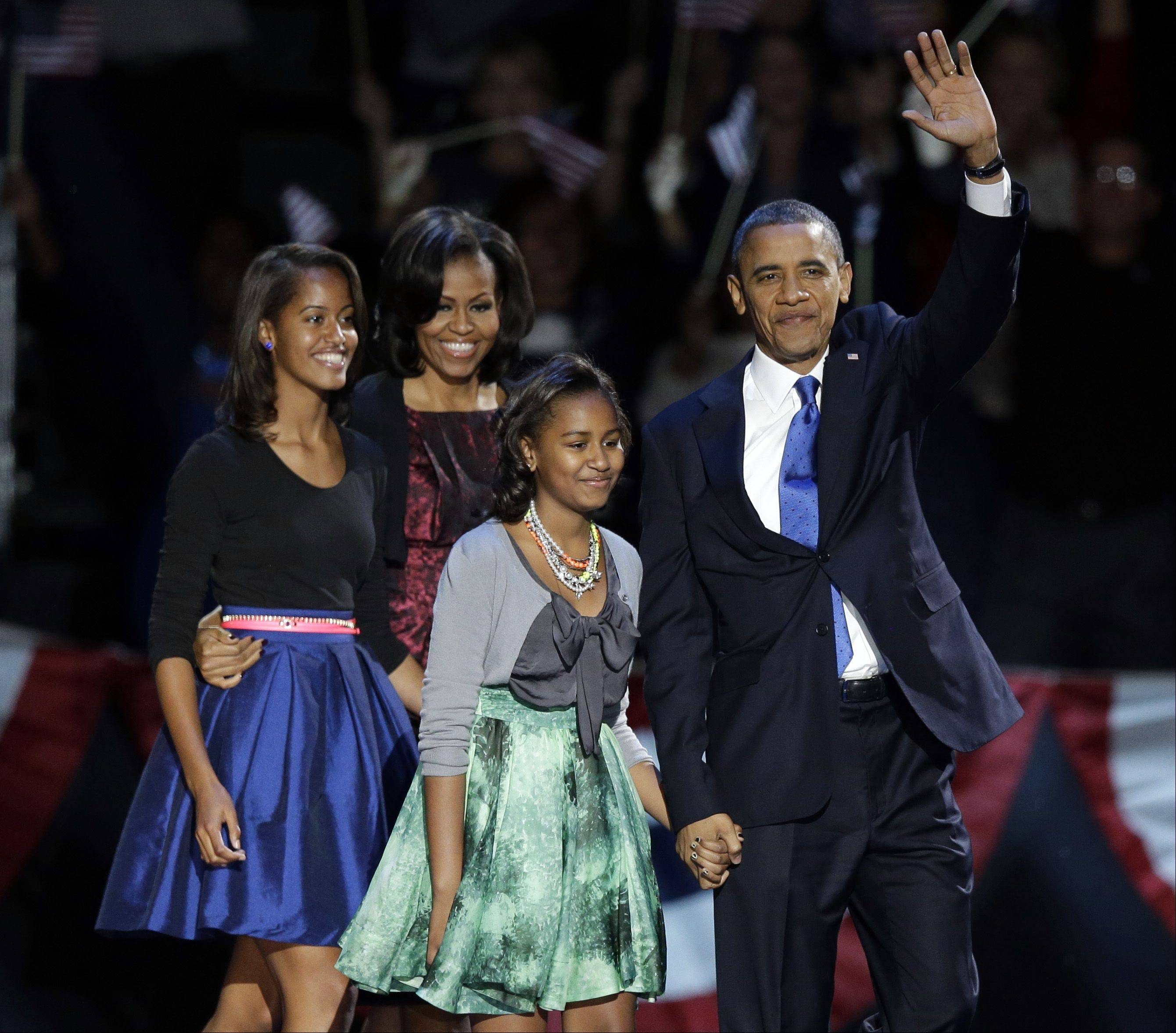 President Barack Obama waves as he walks on stage with first lady Michelle Obama and daughters Malia and Sasha at his election night party Wednesday, Nov. 7, 2012, in Chicago.