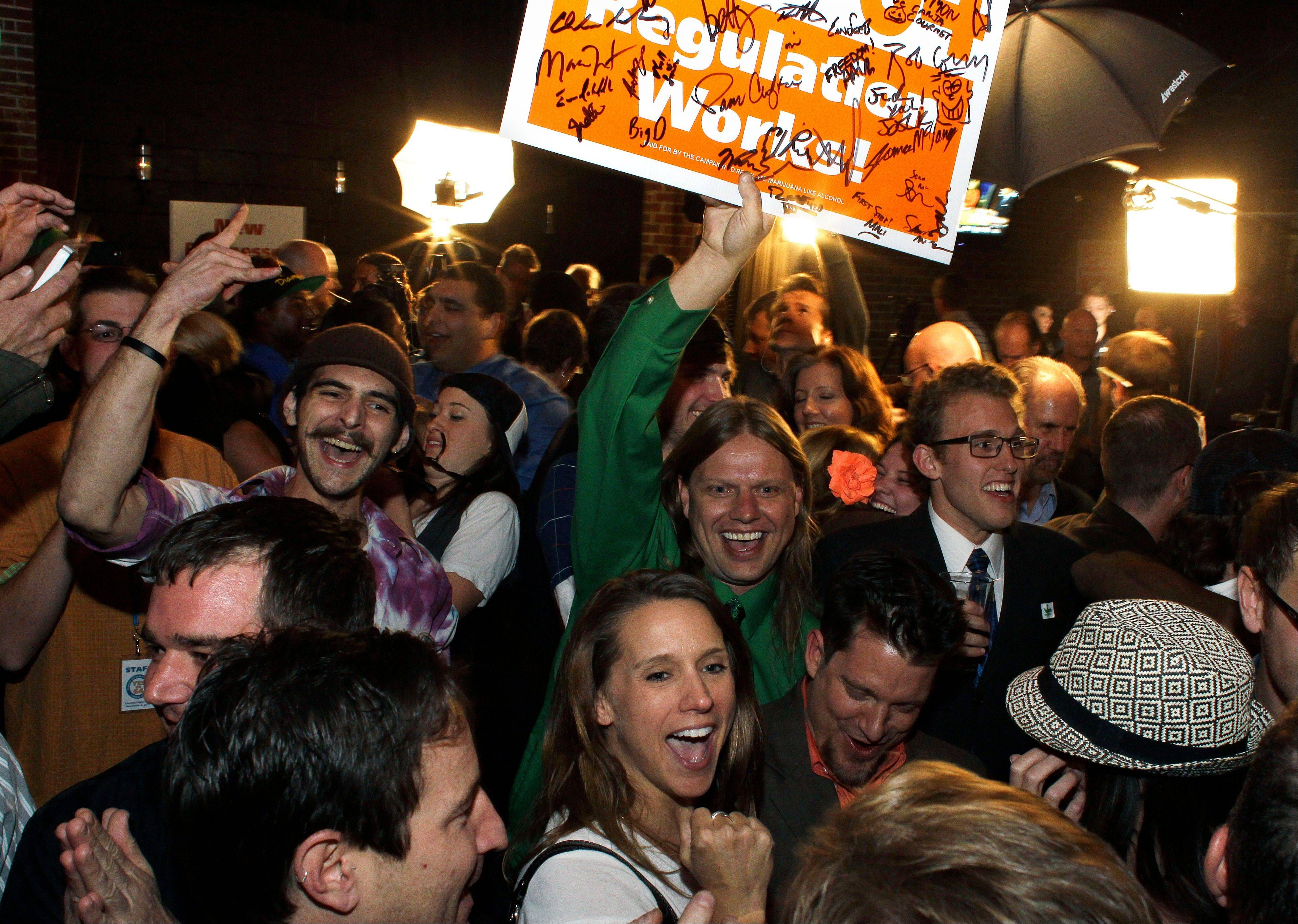People attending an Amendment 64 watch party in a bar celebrate after a local television station announced the marijuana amendment's passage, in Denver, Colo., Tuesday, Nov. 6, 2012. The amendment would make it legal in Colorado for individuals to possess and for businesses to sell marijuana for recreational use.