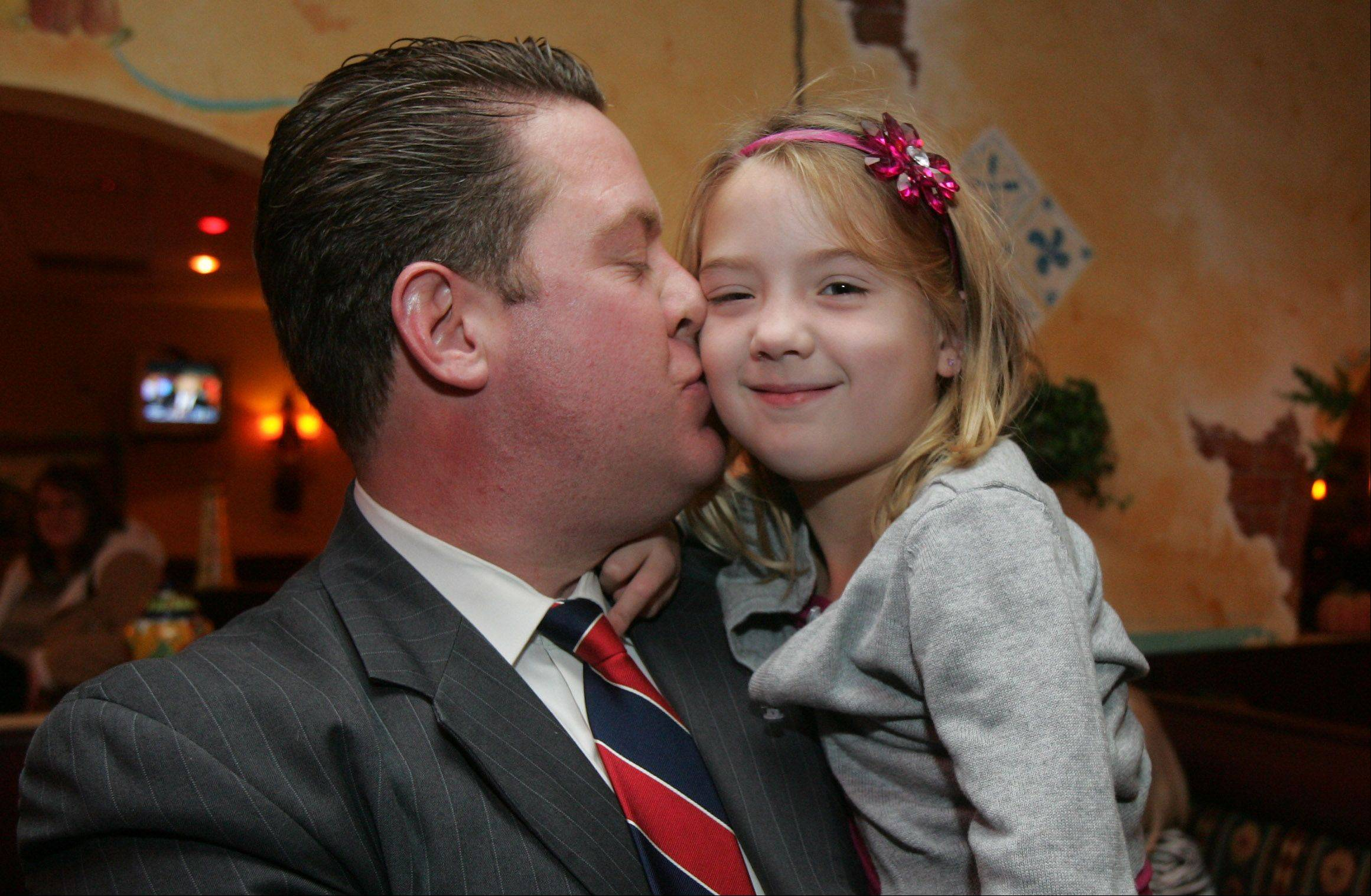 Republican candidate Mike Nerheim kisses his daughter, Grace, 5, as he monitors election results at Tacos El Norte in Gurnee Tuesday in the Lake County State's Attorney race. Nerheim won the election.