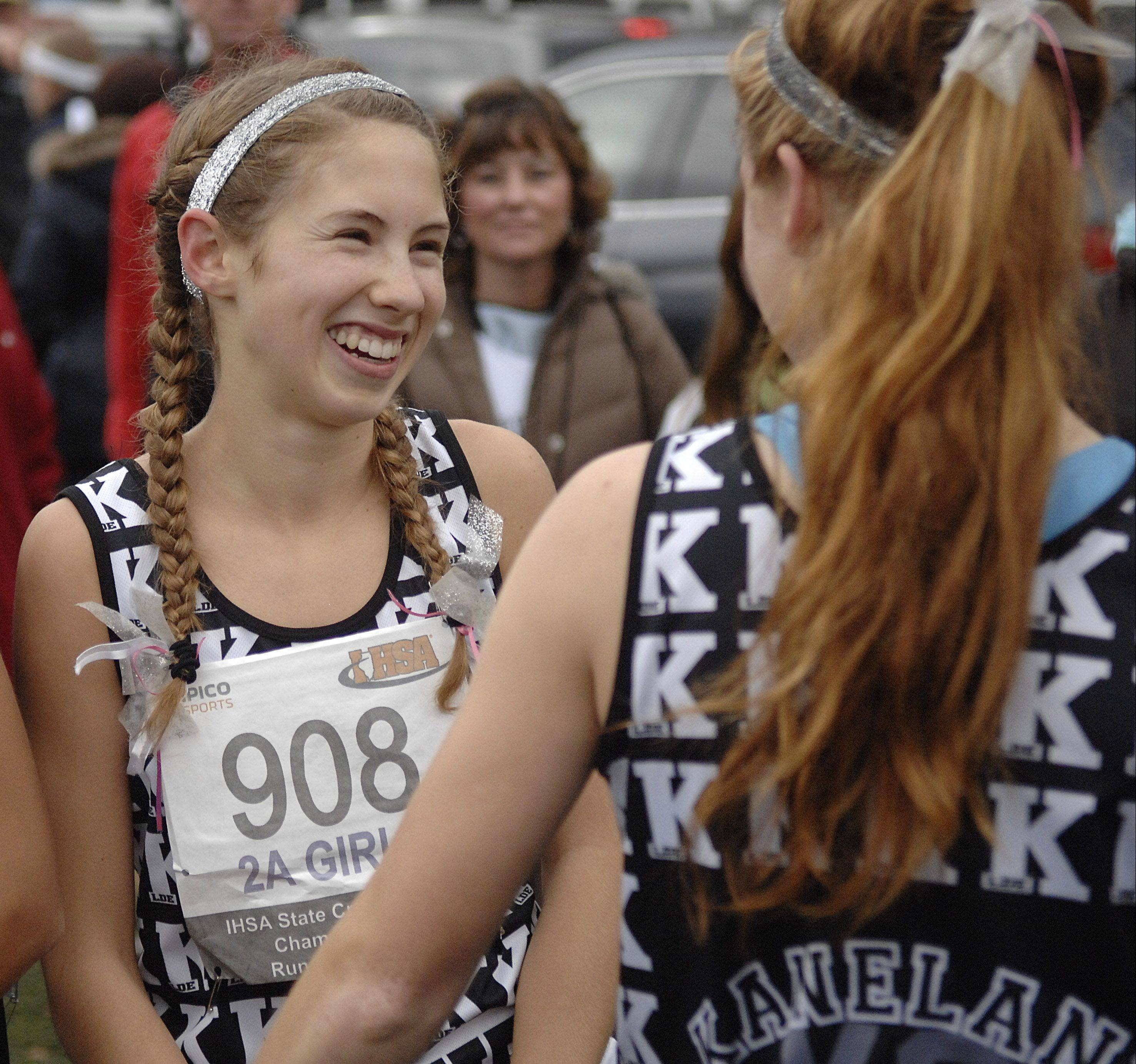 There were plenty of smiles and hugs for Kaneland's Victoria Clinton after the sophomore won the Class 2A state cross country title Saturday in Peoria. Teammate Aislinn Losdwig gives Clinton a hug after the Knights' No. 1 runner pulled away from the field.