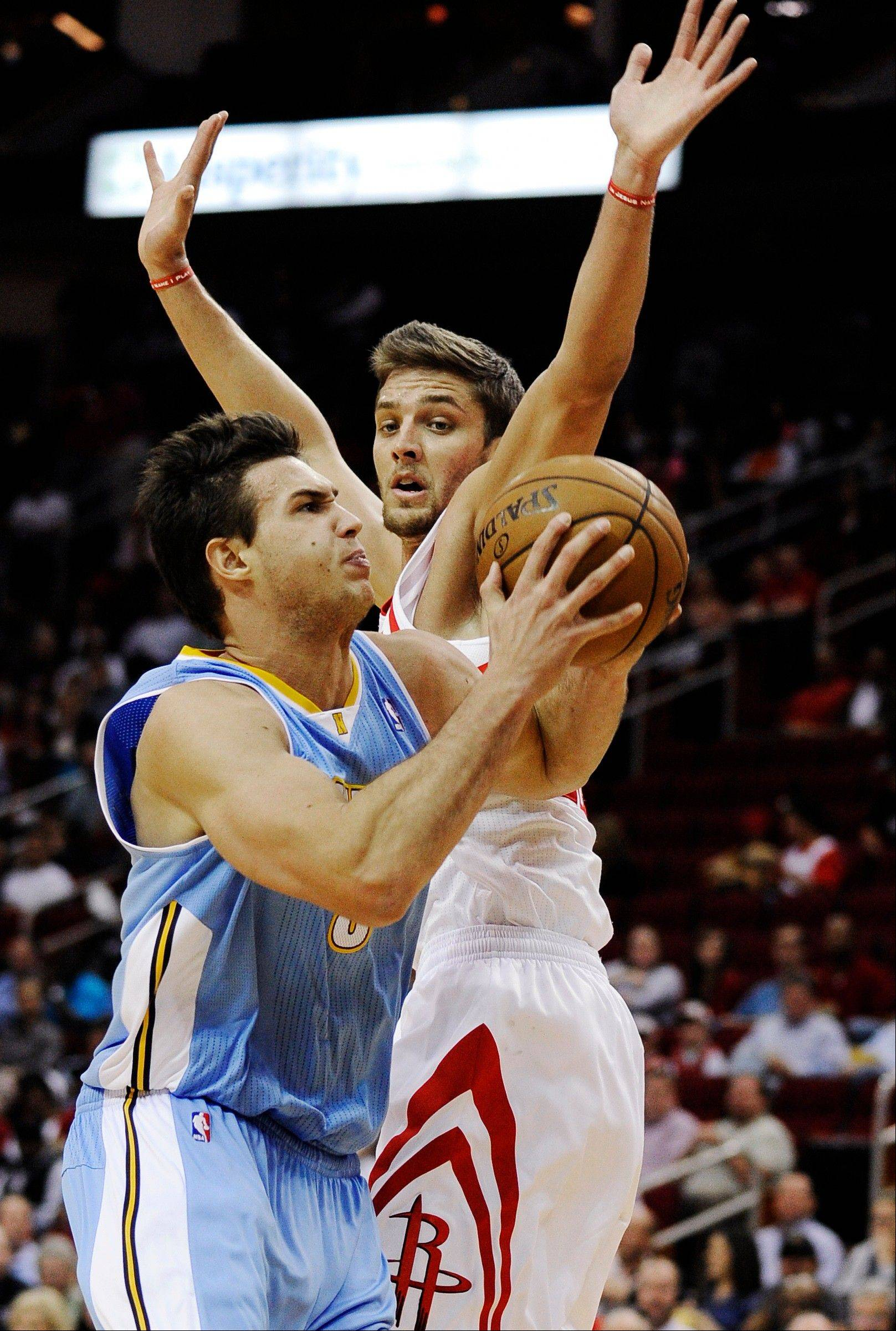 The Denver Nuggets' Danilo Gallinari, left, drives to the basket against Houston Rockets' Chandler Parsons Wednesday during the first half in Houston.