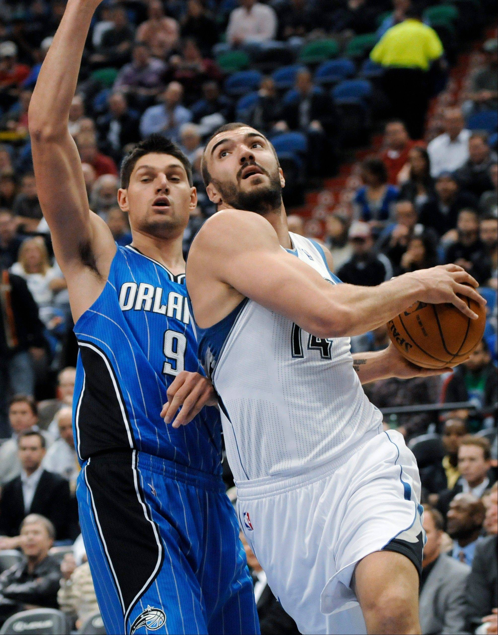 The Minnesota Timberwolves' Nikola Pekovic, right, eyes the basket as the Orlando Magic's Nikola Vucevic defends Wednesday during the first half in Minneapolis.